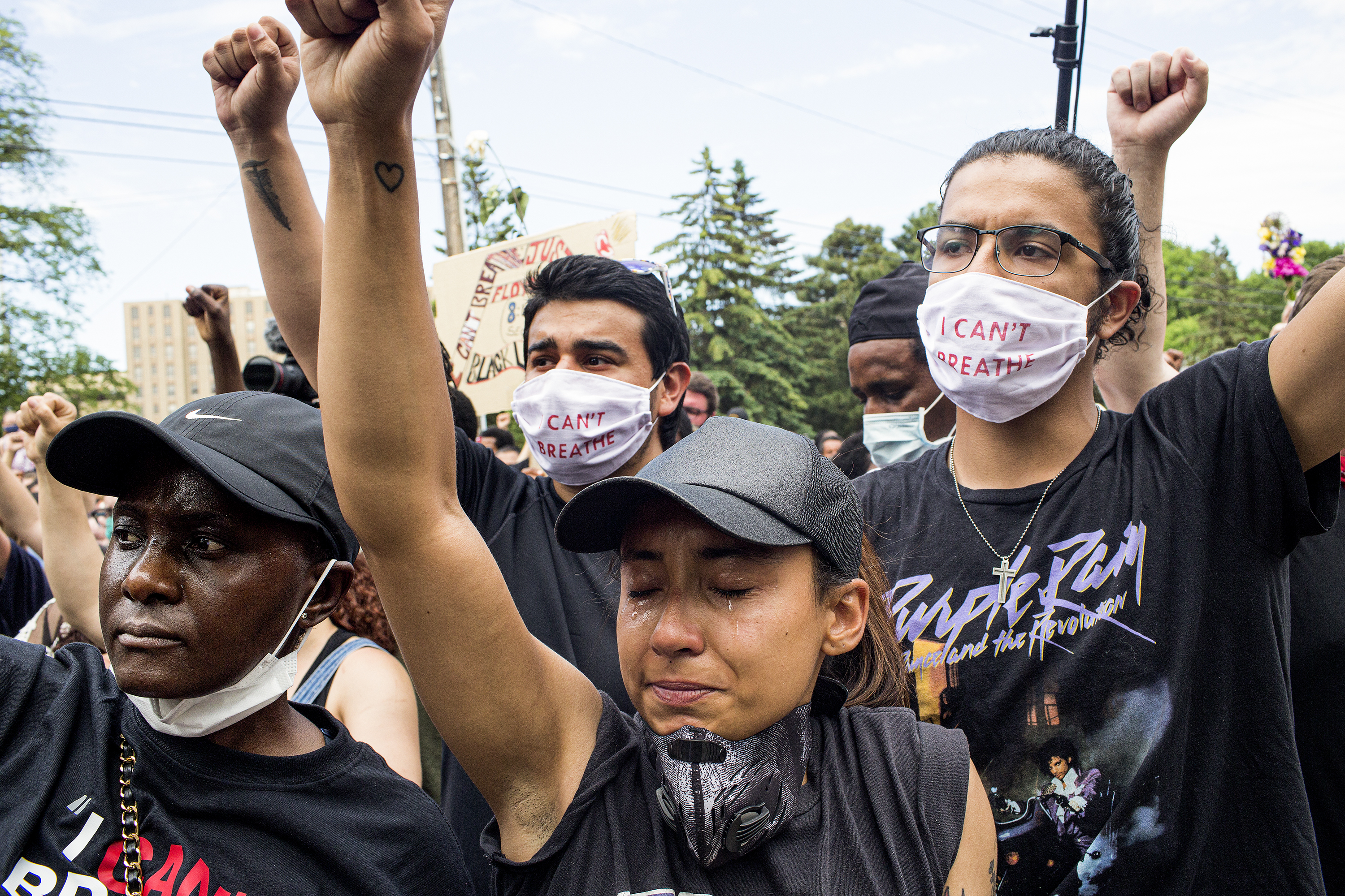 A group of people, men and women, of all ethnicities, dressed in black and wearing masks, raise their fists.