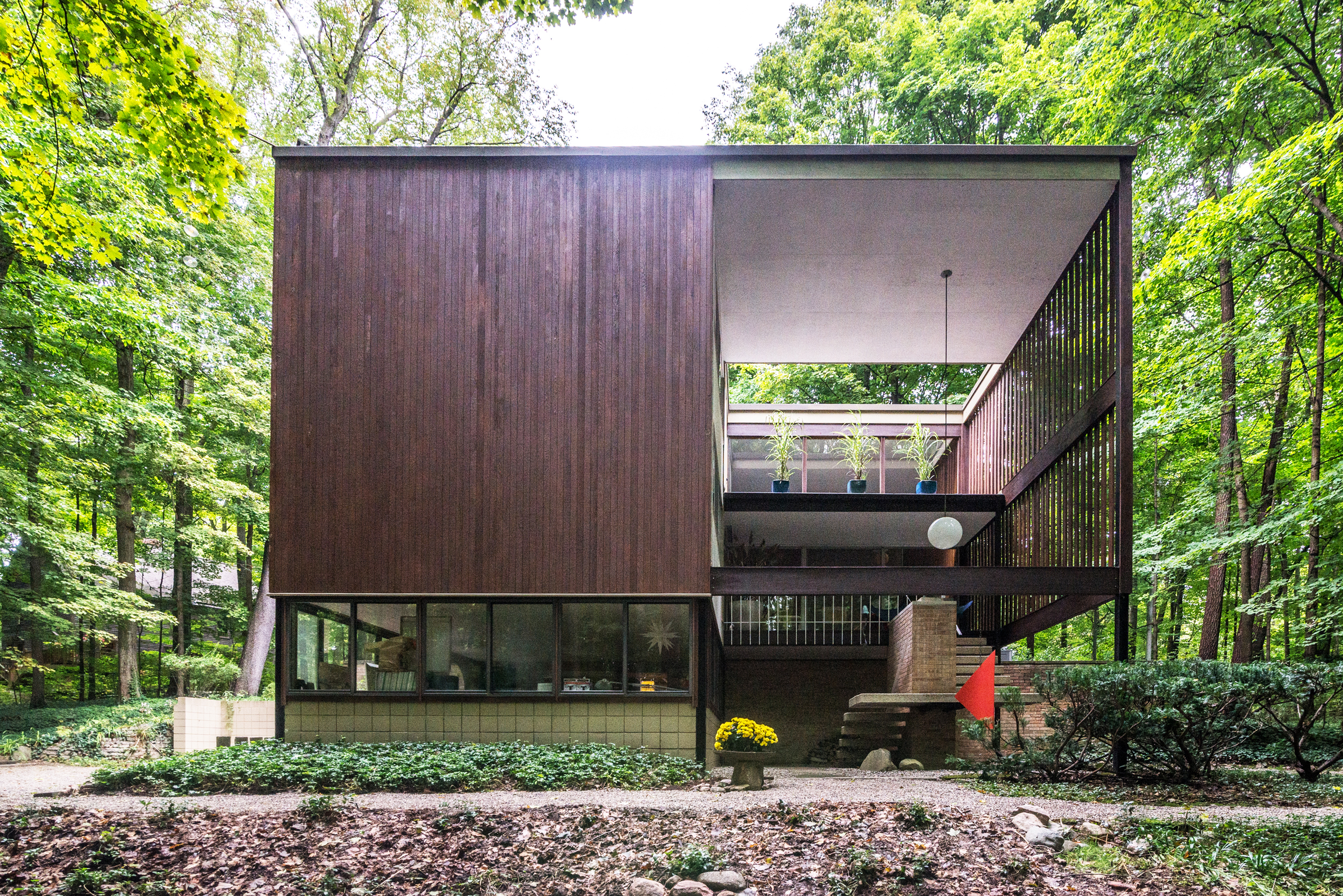 A geometric home with a solid side with wood siding and an 'open' side with a lofted living space. The home is surrounded by woods.