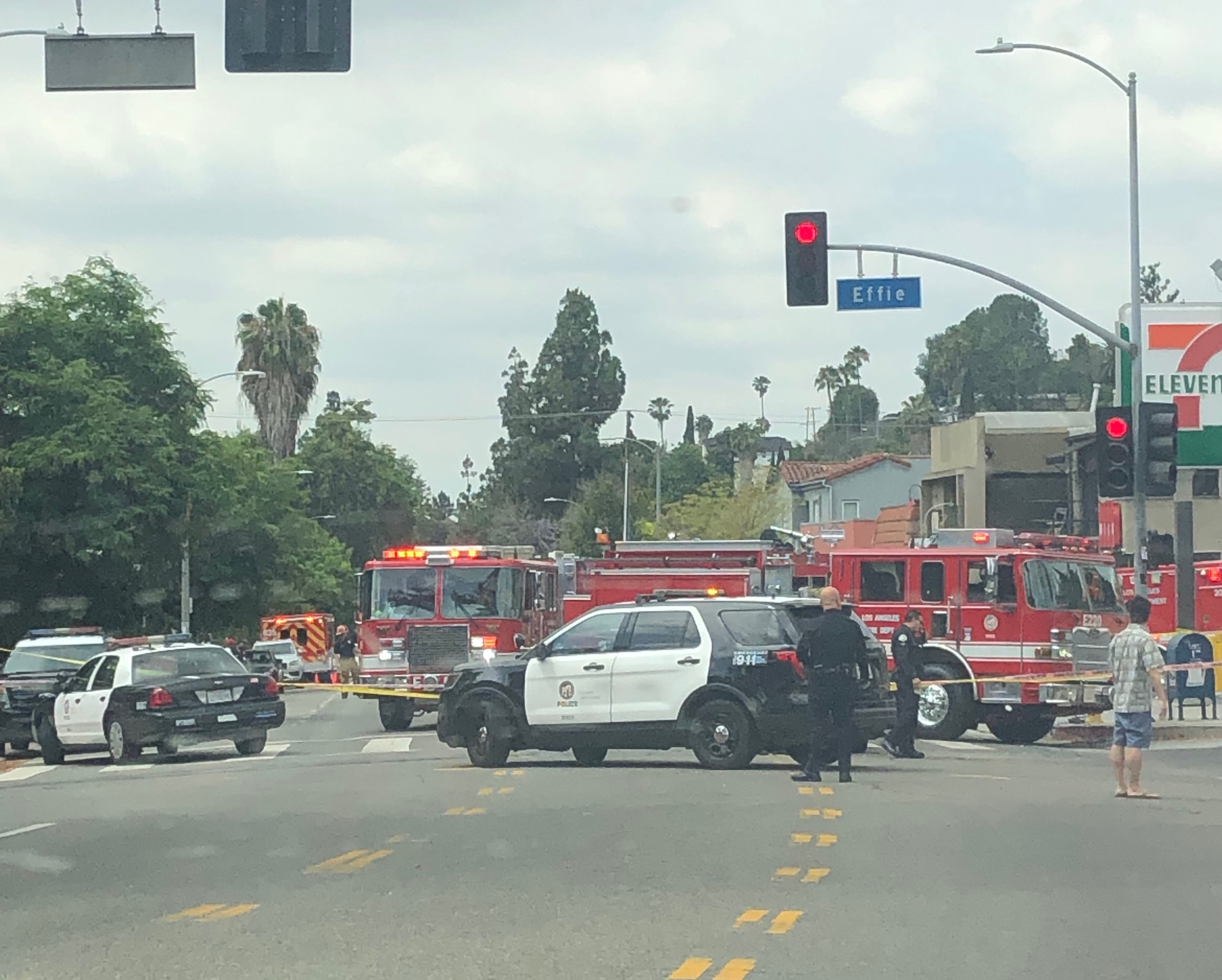 A photo of a police line in front of a car crash at a restaurant.