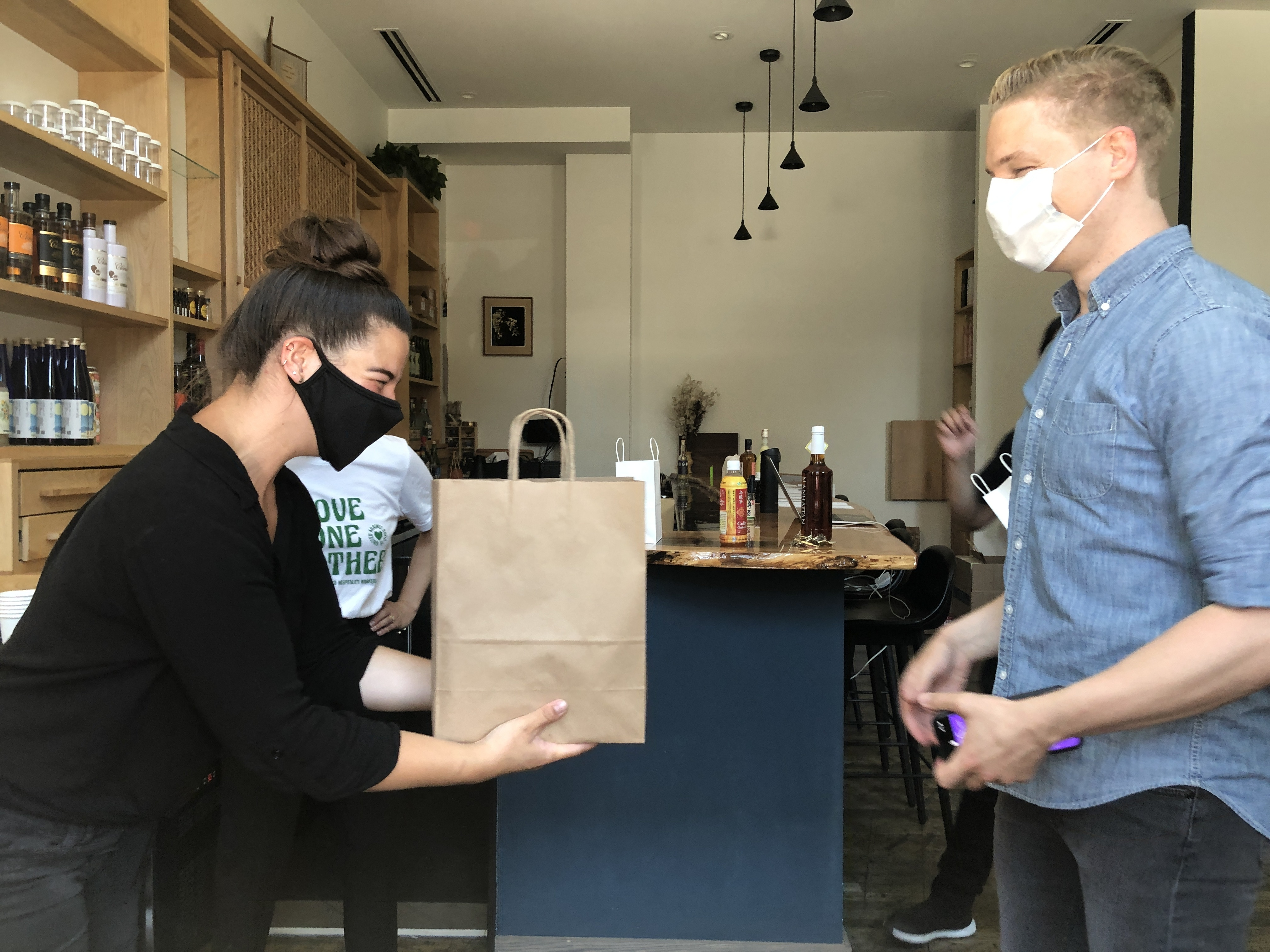 A person wearing black hands another person wearing a button down shirt a brown bag with handle.