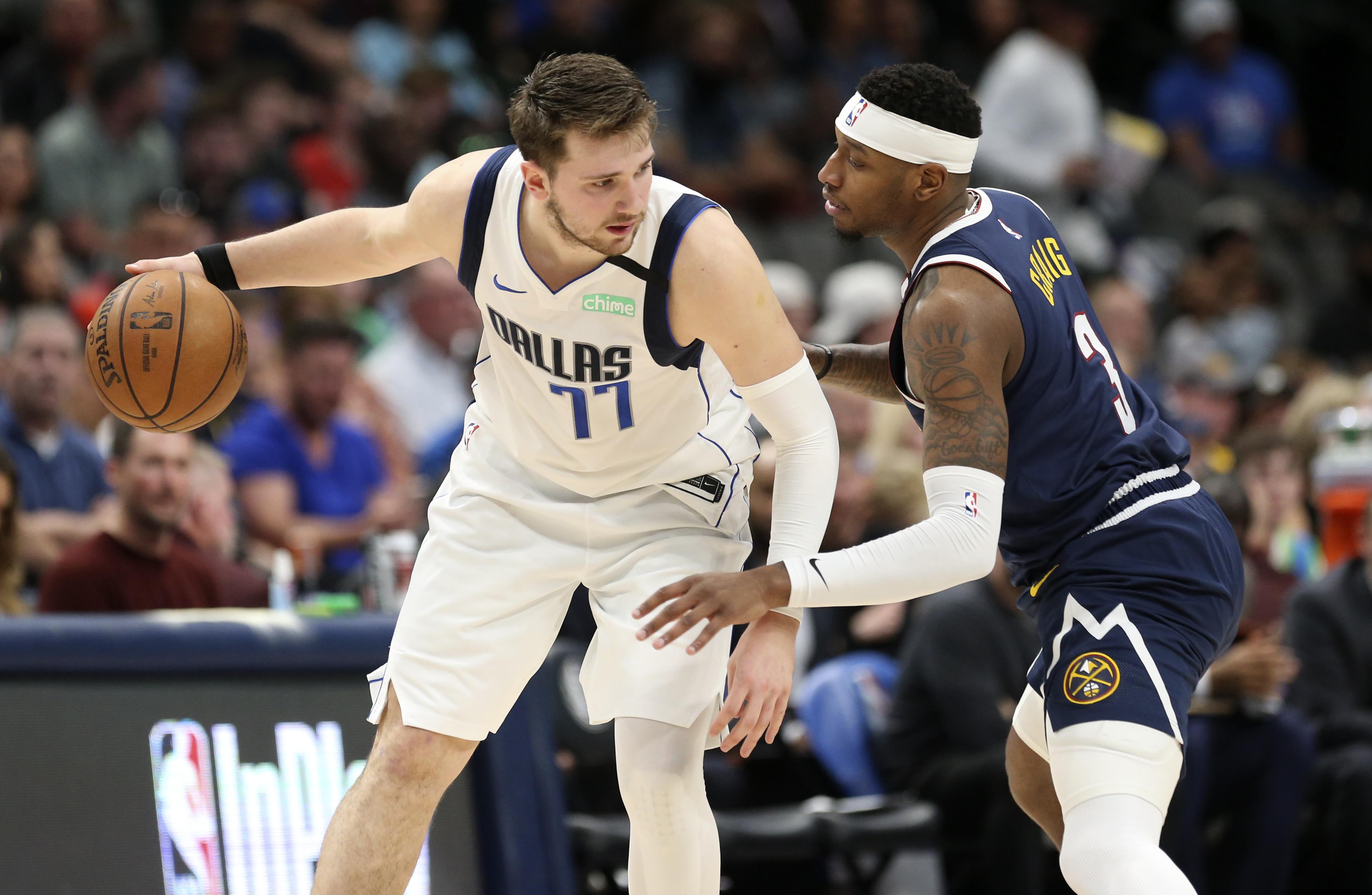 Dallas Mavericks guard Luka Doncic dribbles as Denver Nuggets forward Torrey Craig defends during the second half at American Airlines Center.