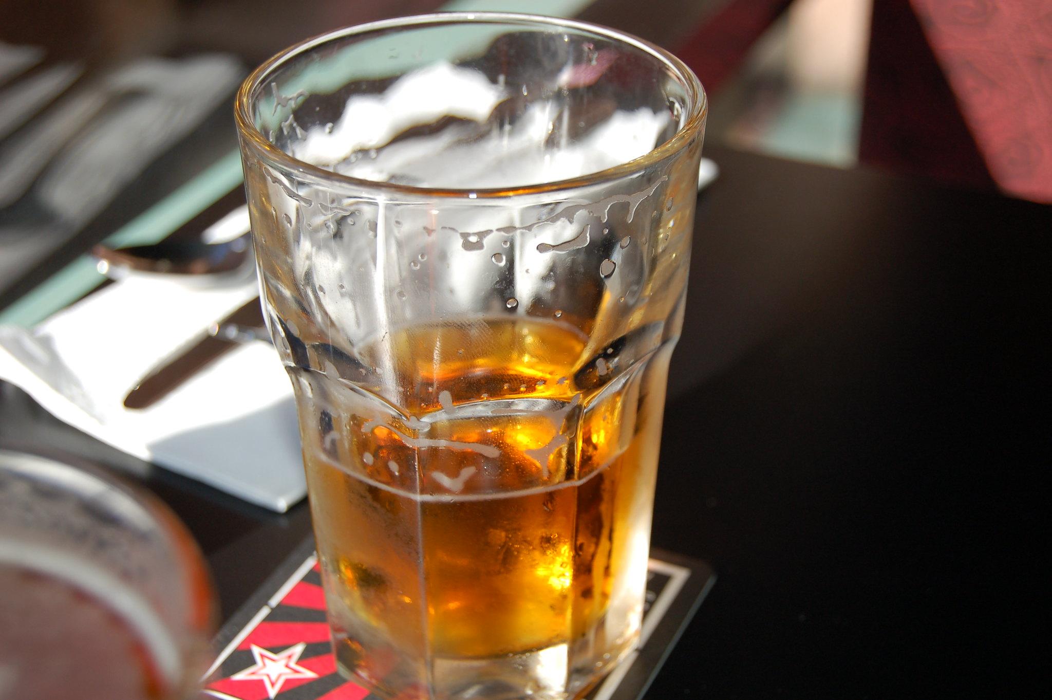A half-drank beer sits on a dark bar.