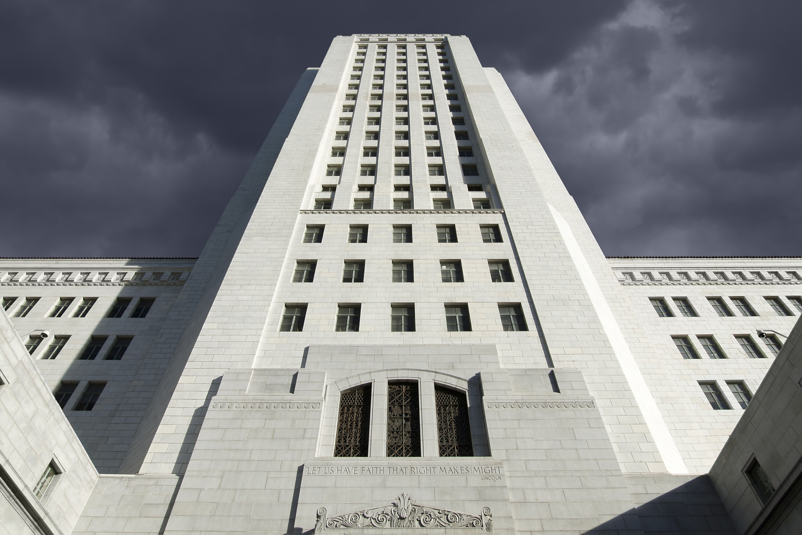 A worms-eye view of a looming white concrete building, L.A. City Hall, many stories high. It feels ominous and foreboding, towering above the viewer's vantage point.