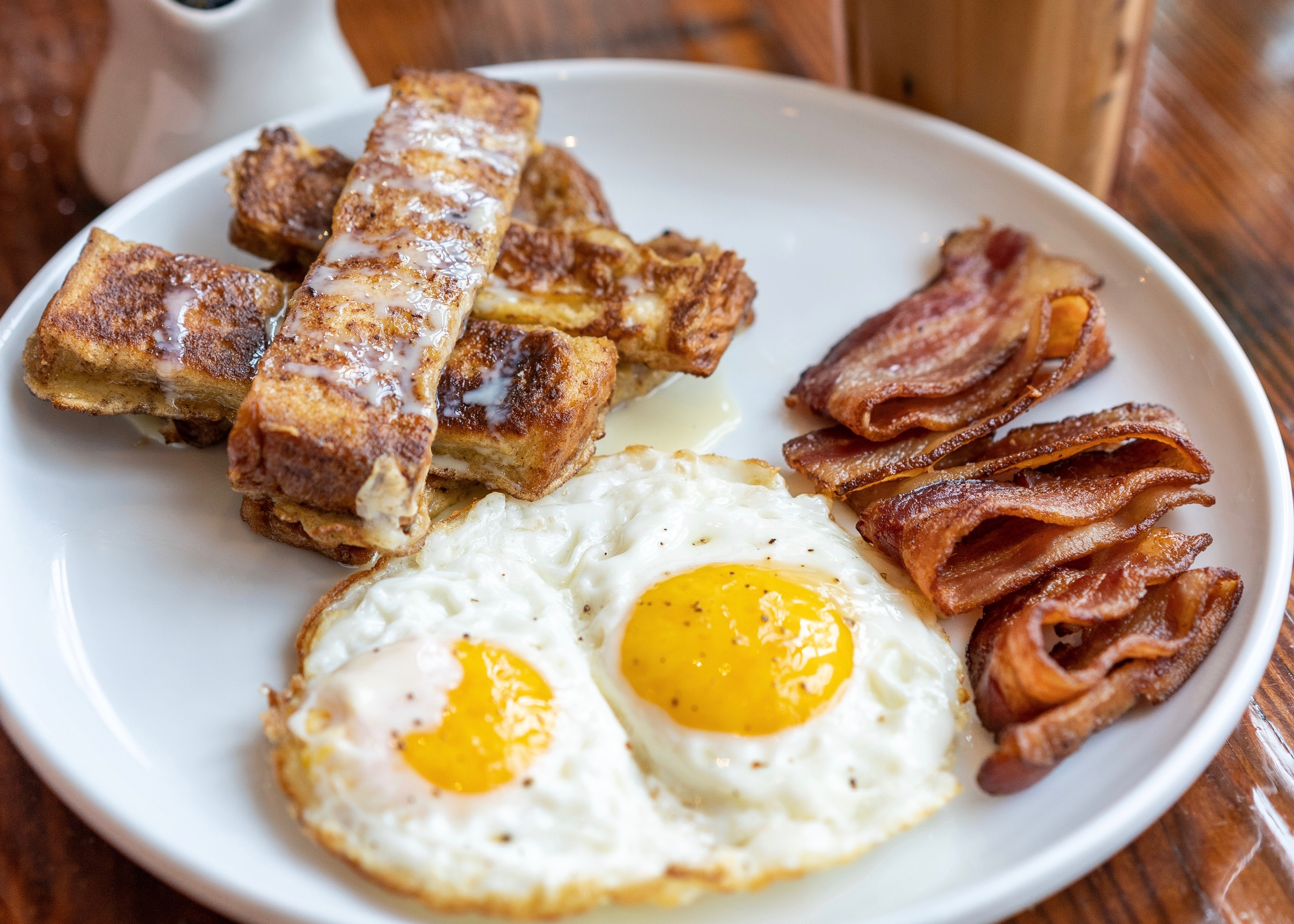 white plate with eggs, bacon, and french toast sticks