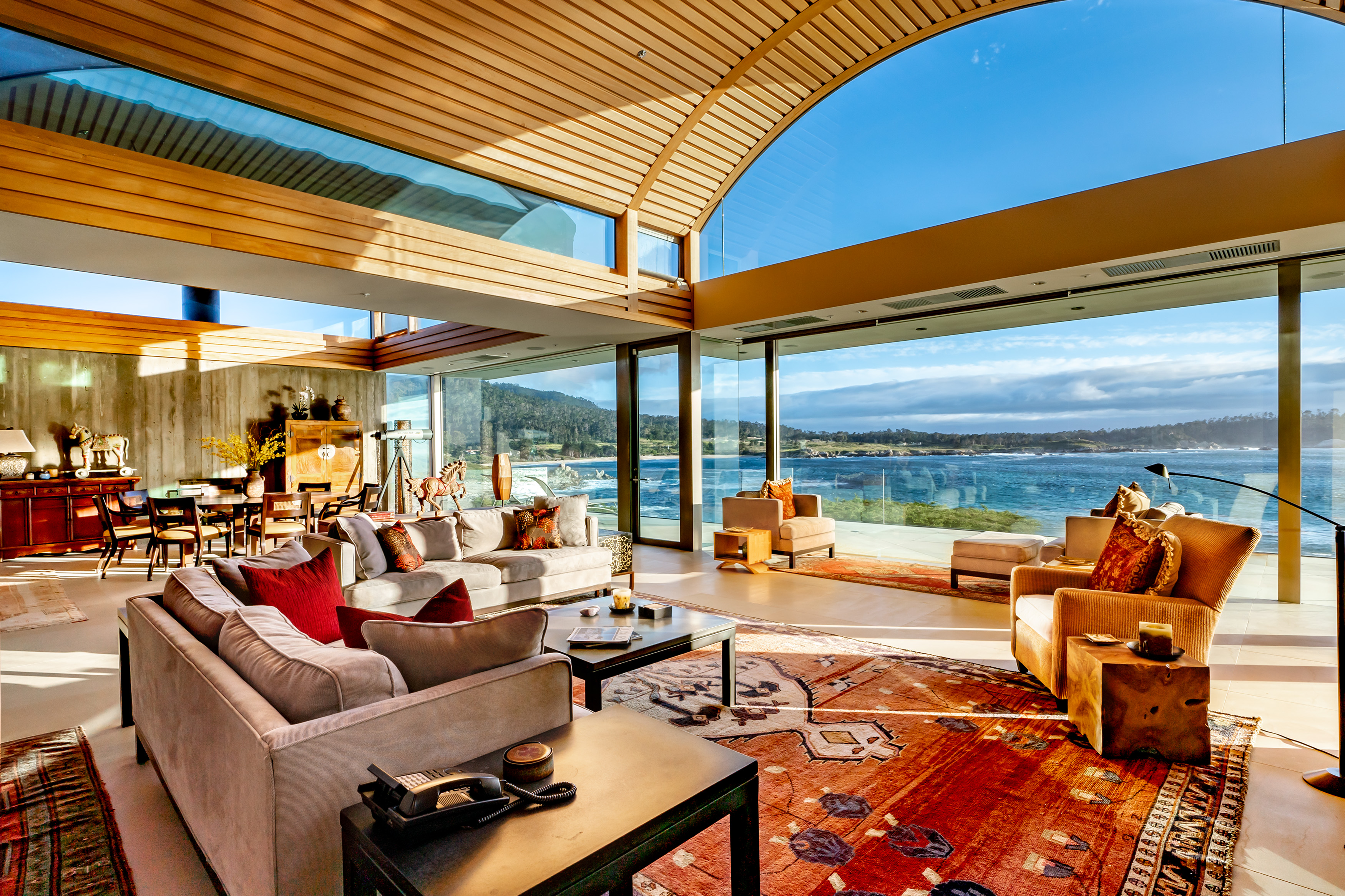 An interior view of a living room in a Carmel house for sale with a barrel vaulted wood ceiling and ocean views. There is a couch and other chairs.