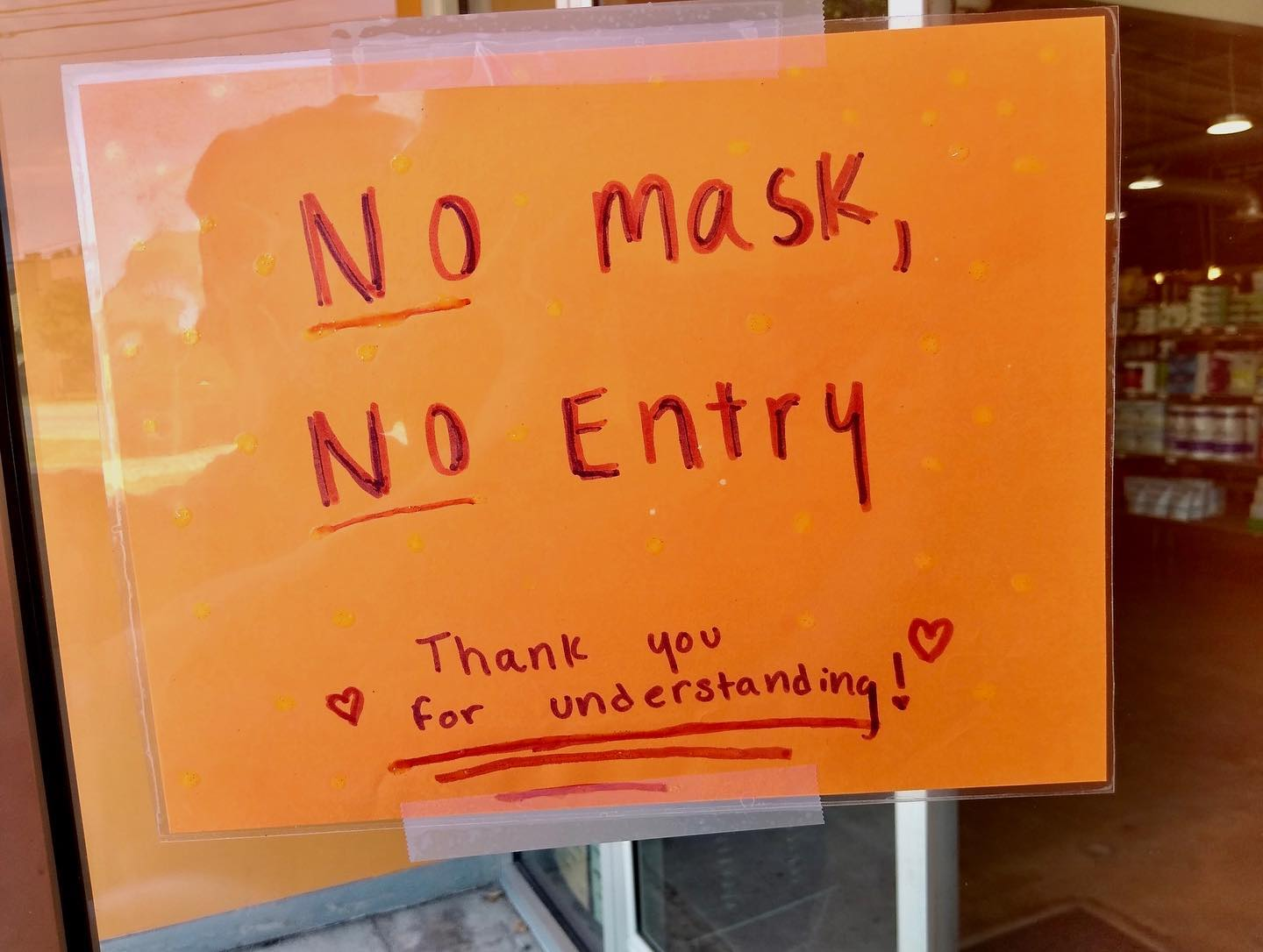 """A handwritten sign on orange paper that says """"No Mask, No Entry. Thank you for your understanding <3"""""""