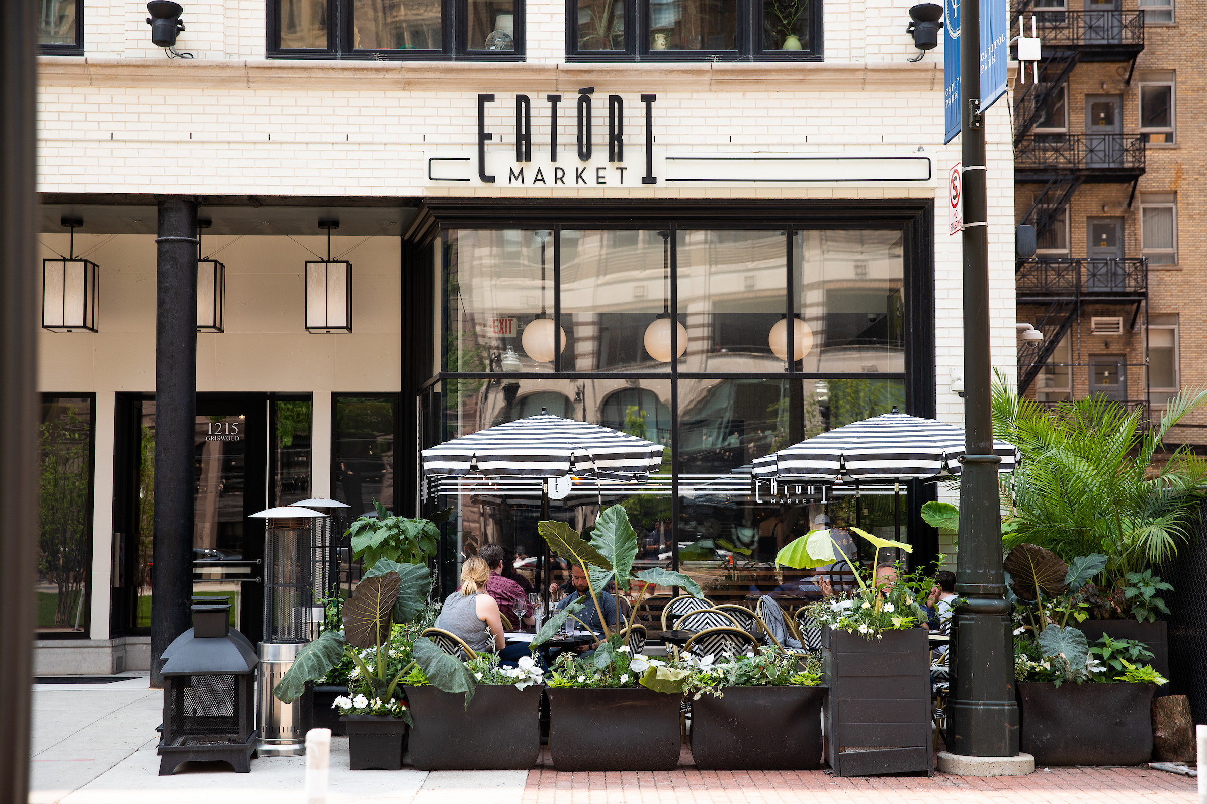 A lush patio with plants and black and white striped umbrellas outside Eatori Market in Capitol Park.