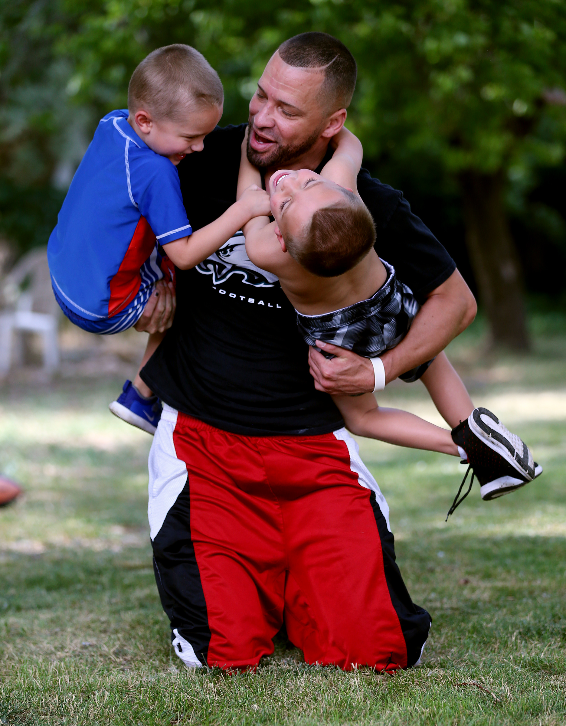 John Chapman wrestles with his boys, Easton and Braxton, as he tries to get them to settle down for a posed photo in their backyard in Holladay on Friday, June 5, 2020.