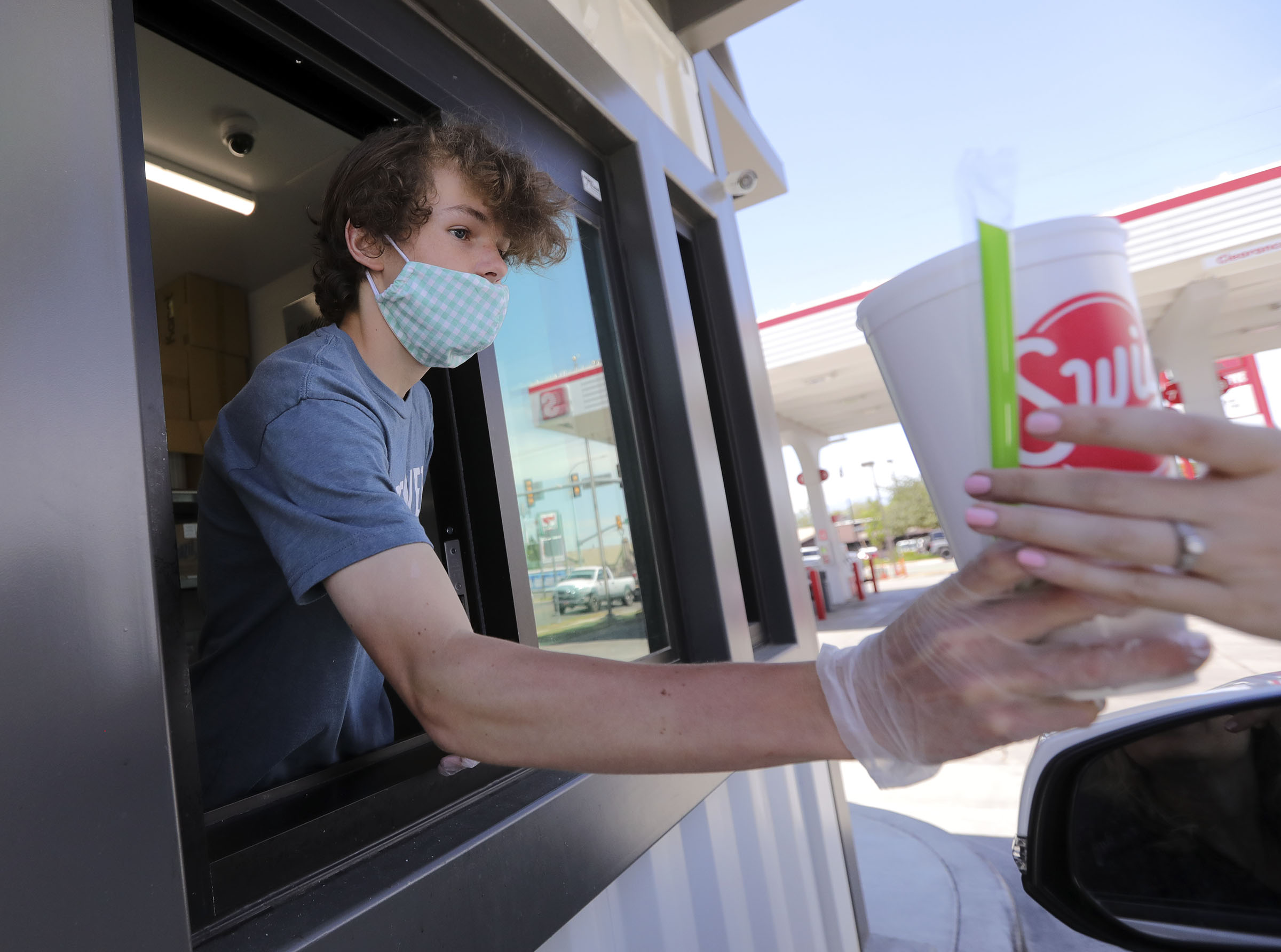 Henry Randle hands out beverages at Swig's drive-thru window in Millcreek on Wednesday, June 3, 2020.