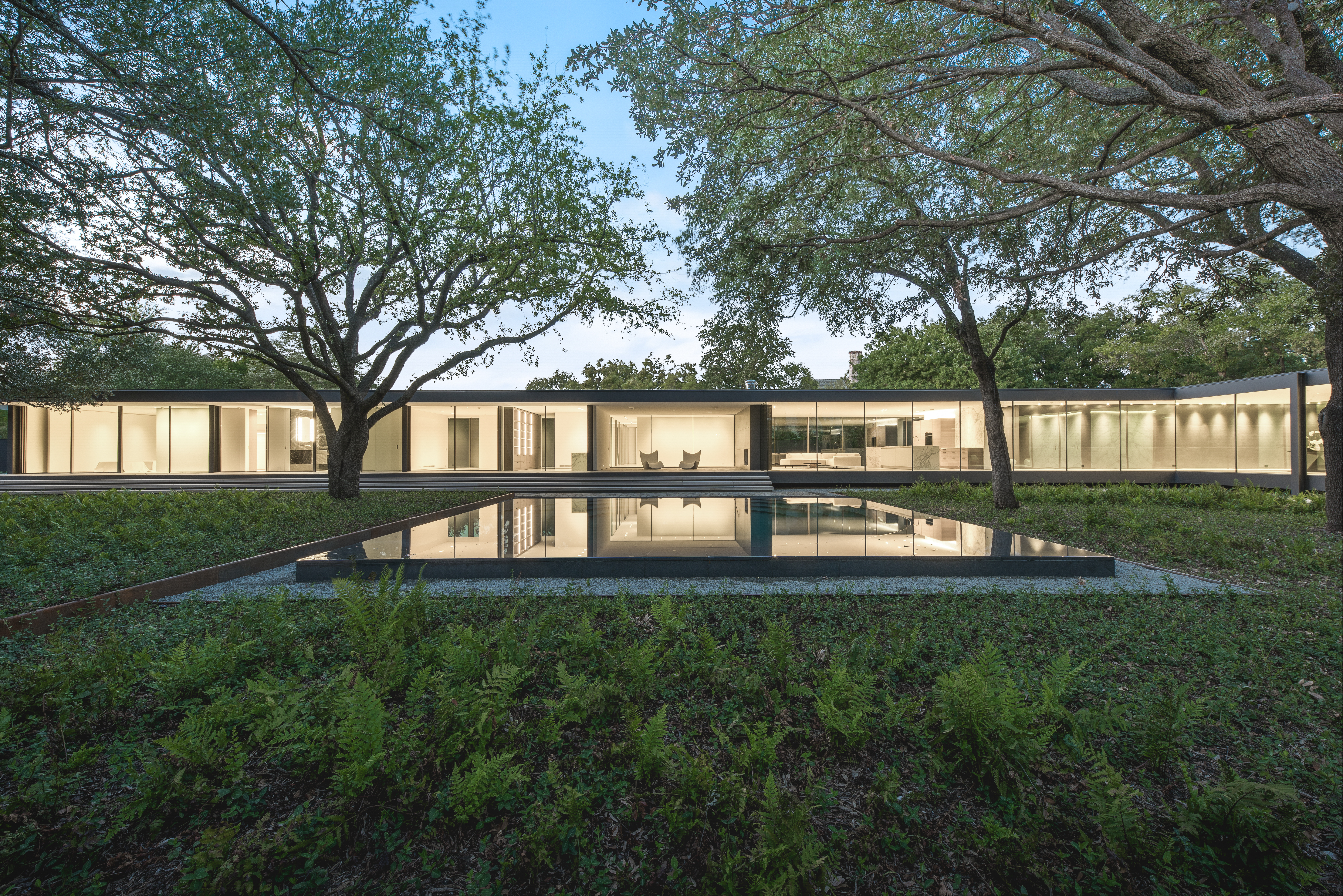 An exterior view of a Dallas, Texas, home for sale that is lit up at dusk. The long horizontal home has a reflecting in front with trees and grass on the side.