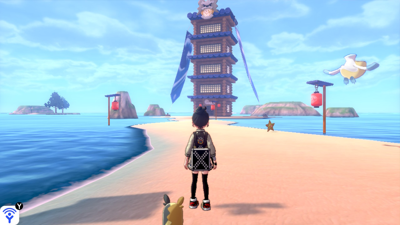 A Pokémon trainer stands on the beach overlooking a large tower