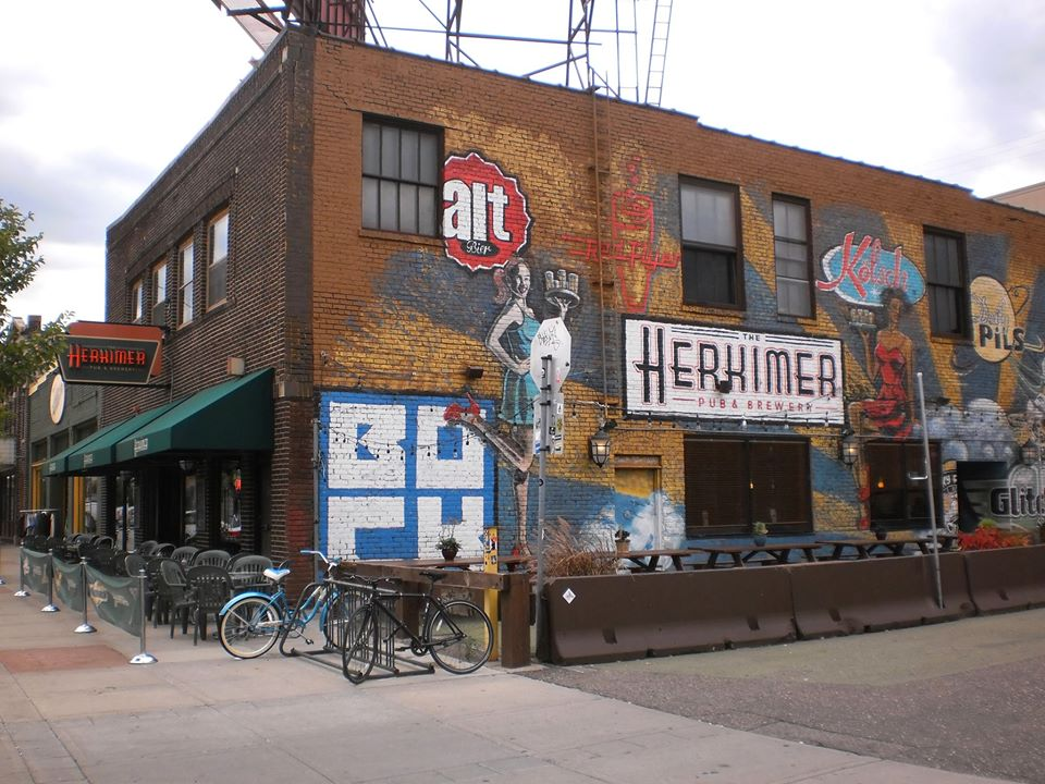 The exterior of the building from last summer, with chairs outside, and a mural on the side of the building