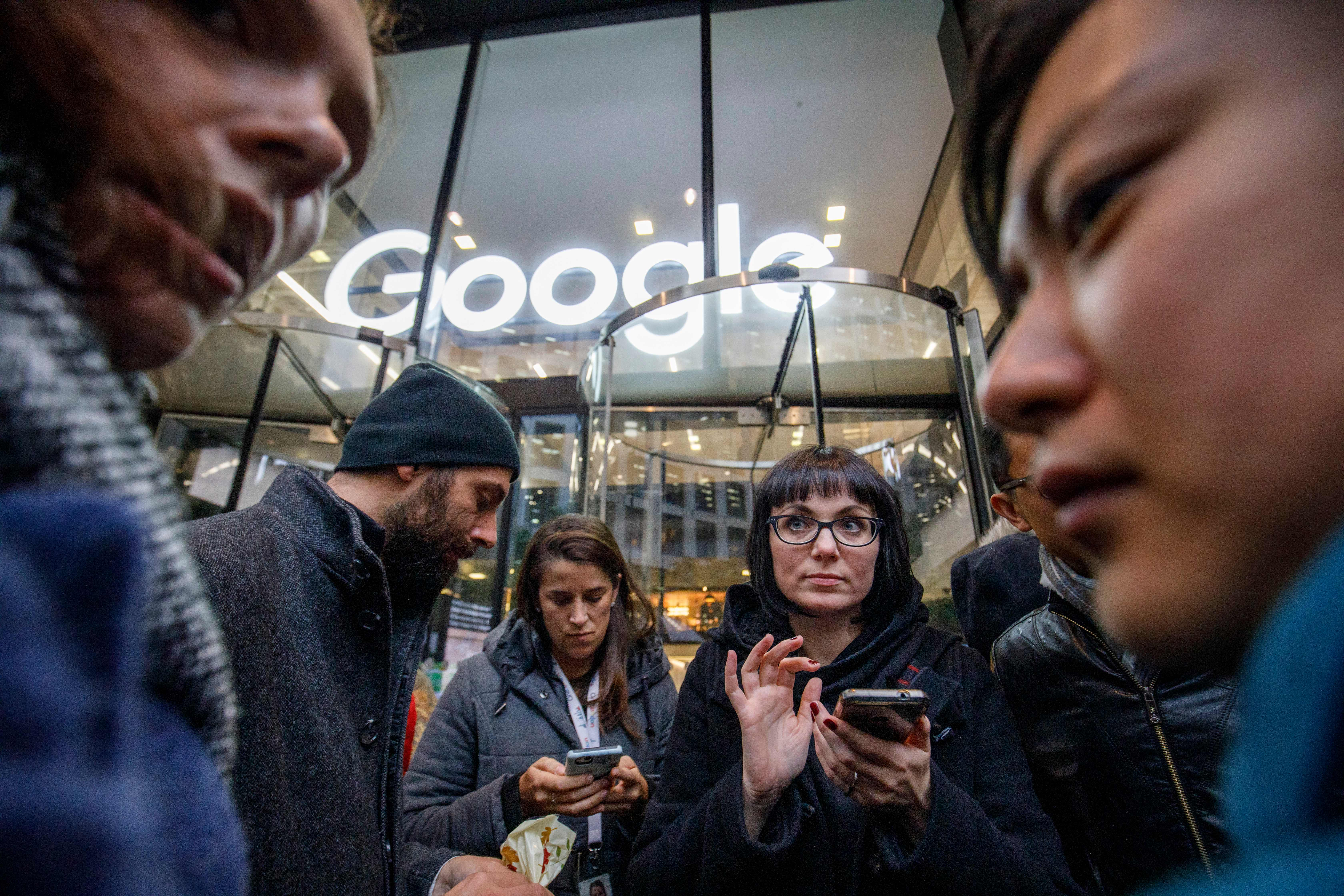 A group of Google employees stands in front of a Google office building in London during a protest.