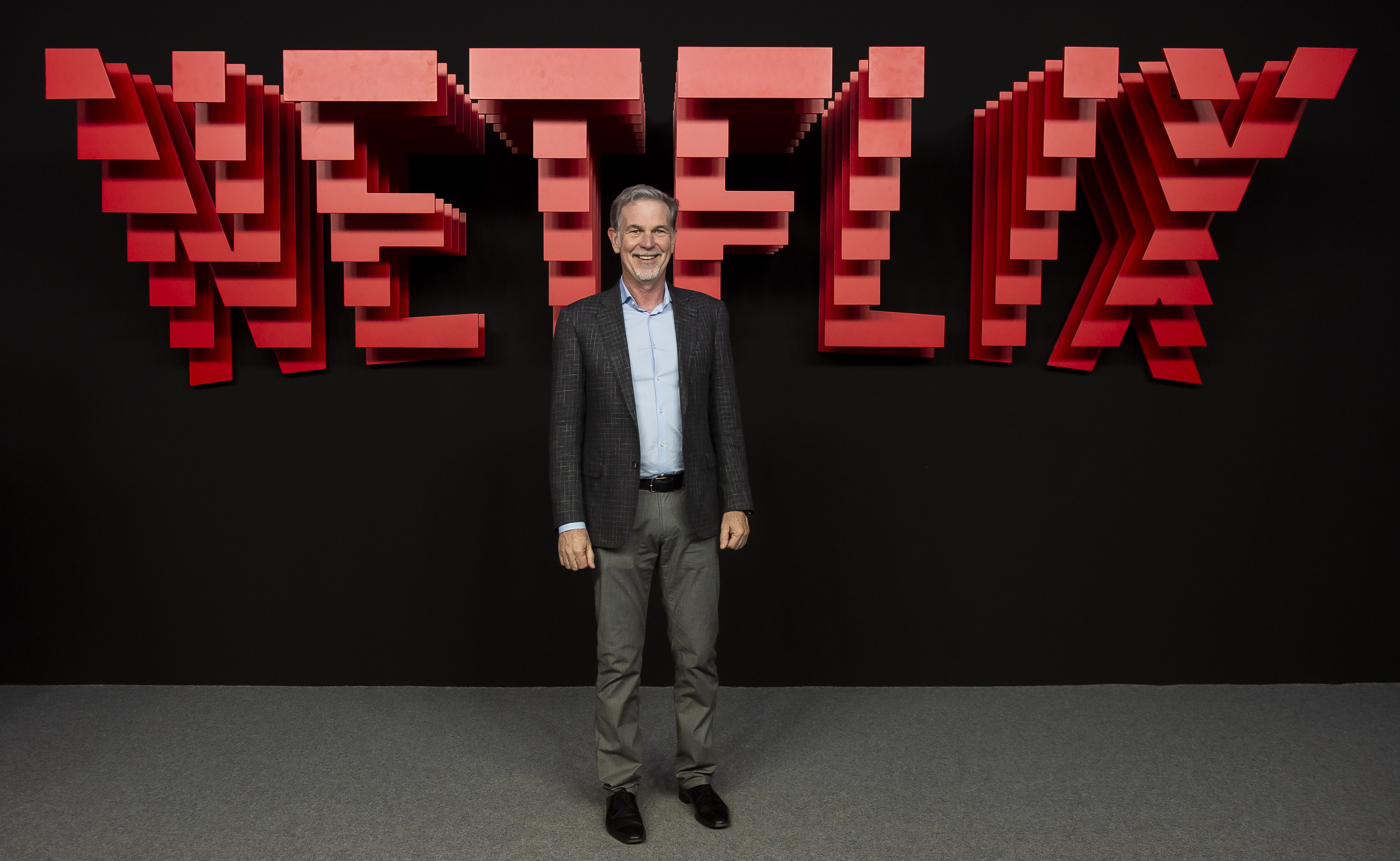 "Netflix CEO Reed Hastings standing in front of a large sign reading ""Netflix."""