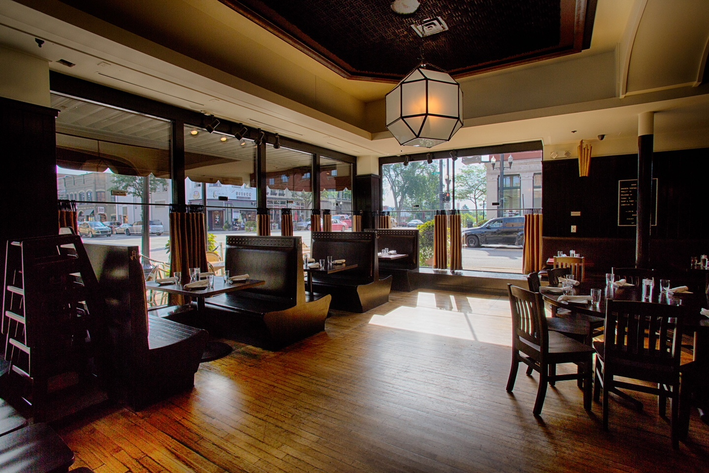 The interior of Diamonds Steak and Seafood in Howell features wood booths and deco, frosted glass light fixtures.
