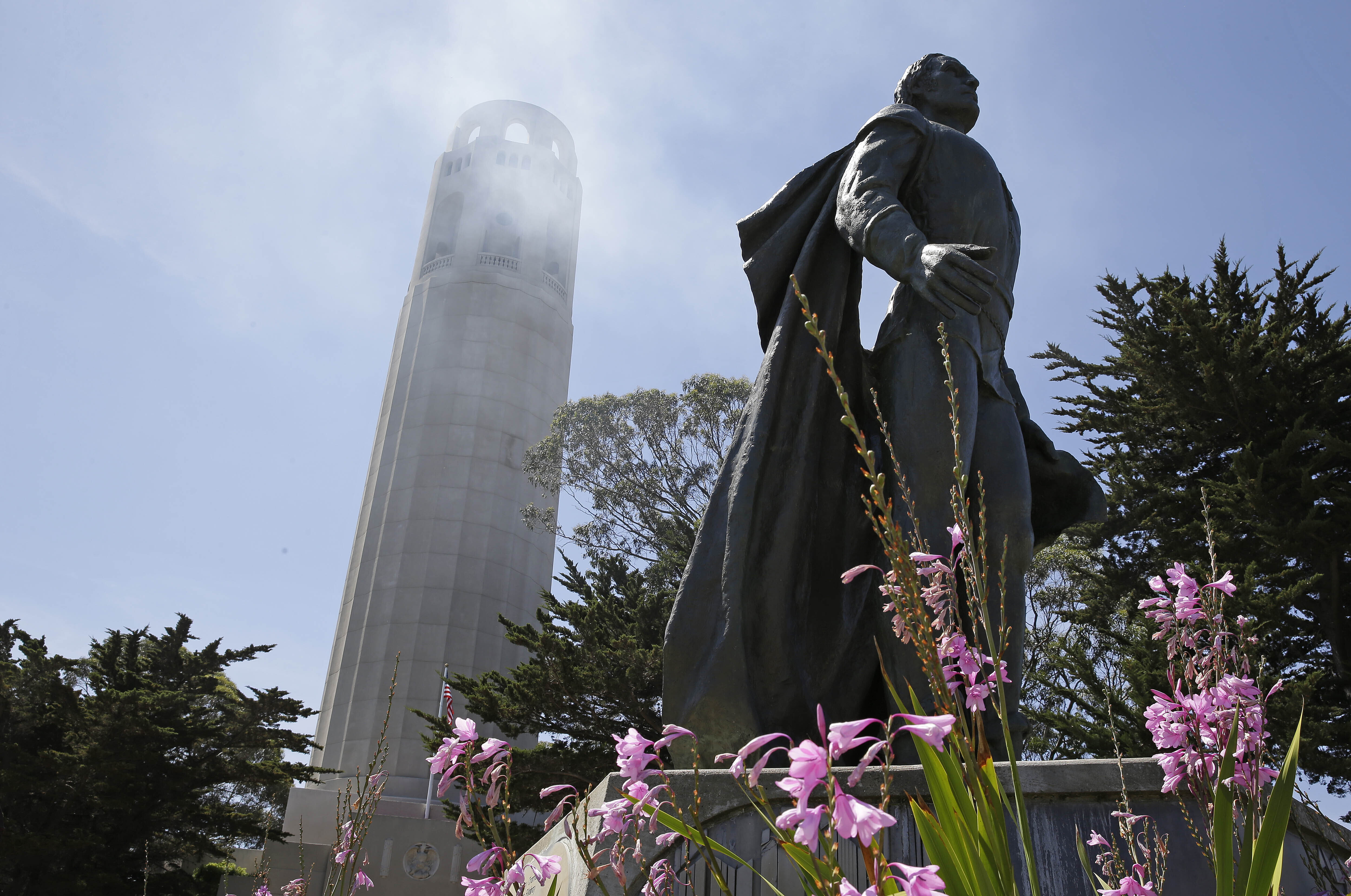 A statue of Christopher Columbus stands beneath Coit Tower in San Francisco