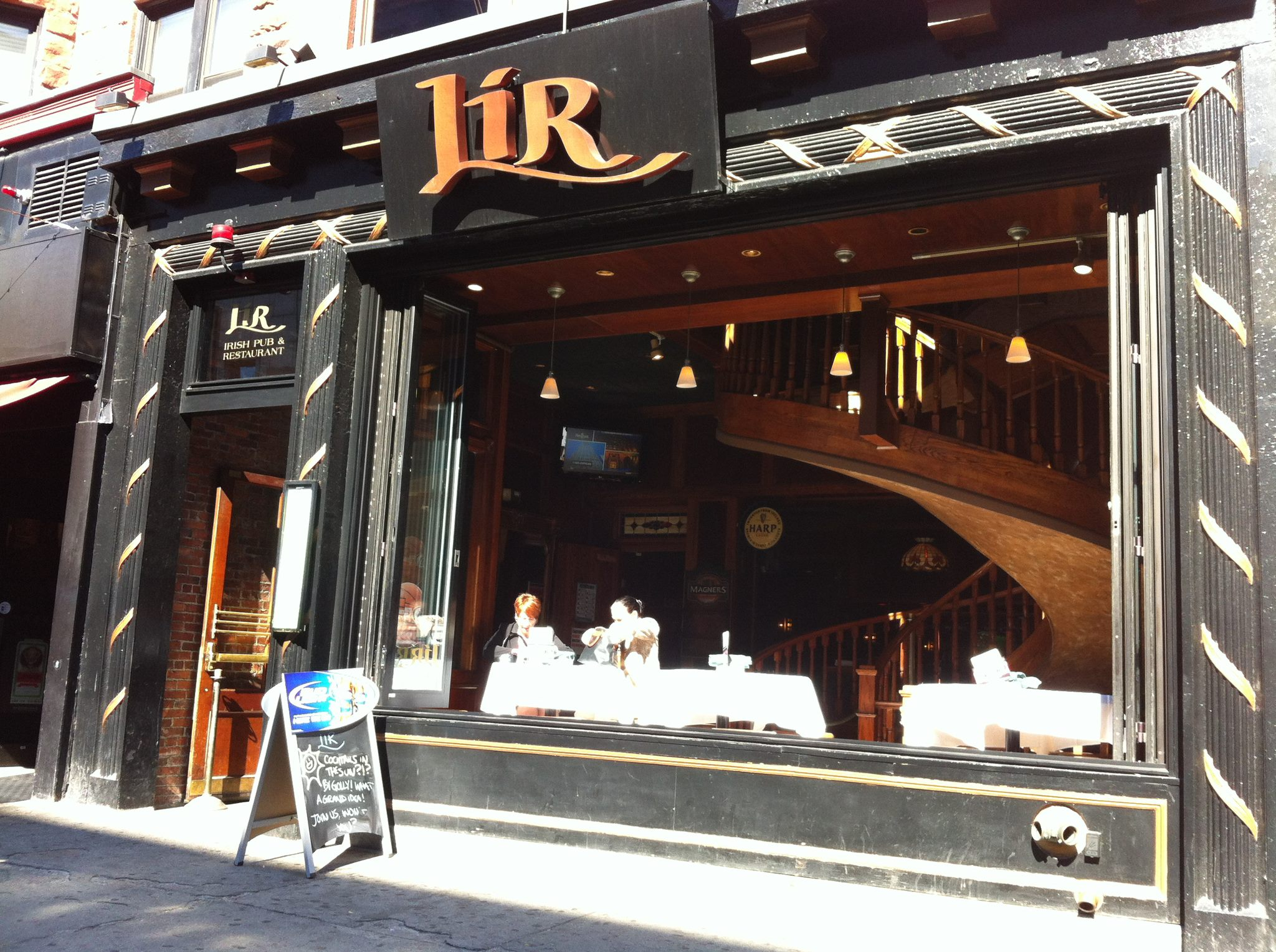 """Exterior of a bar with signage reading """"Lir."""" The exterior is dark wood, and a giant nearly floor-to-ceiling window takes up most of the space, open to the sidewalk."""