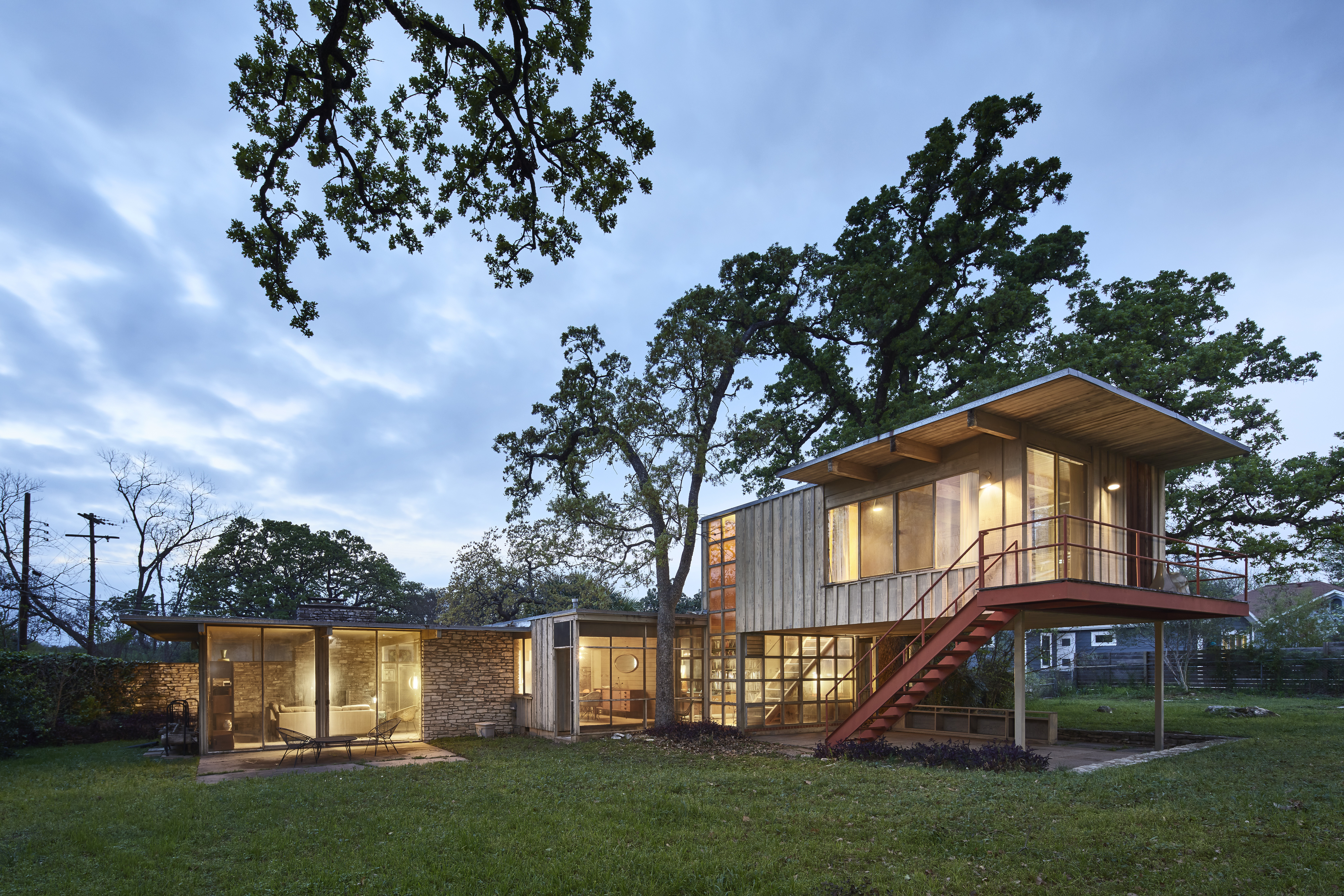 Rectilinear house with an elevated second story with a balcony.