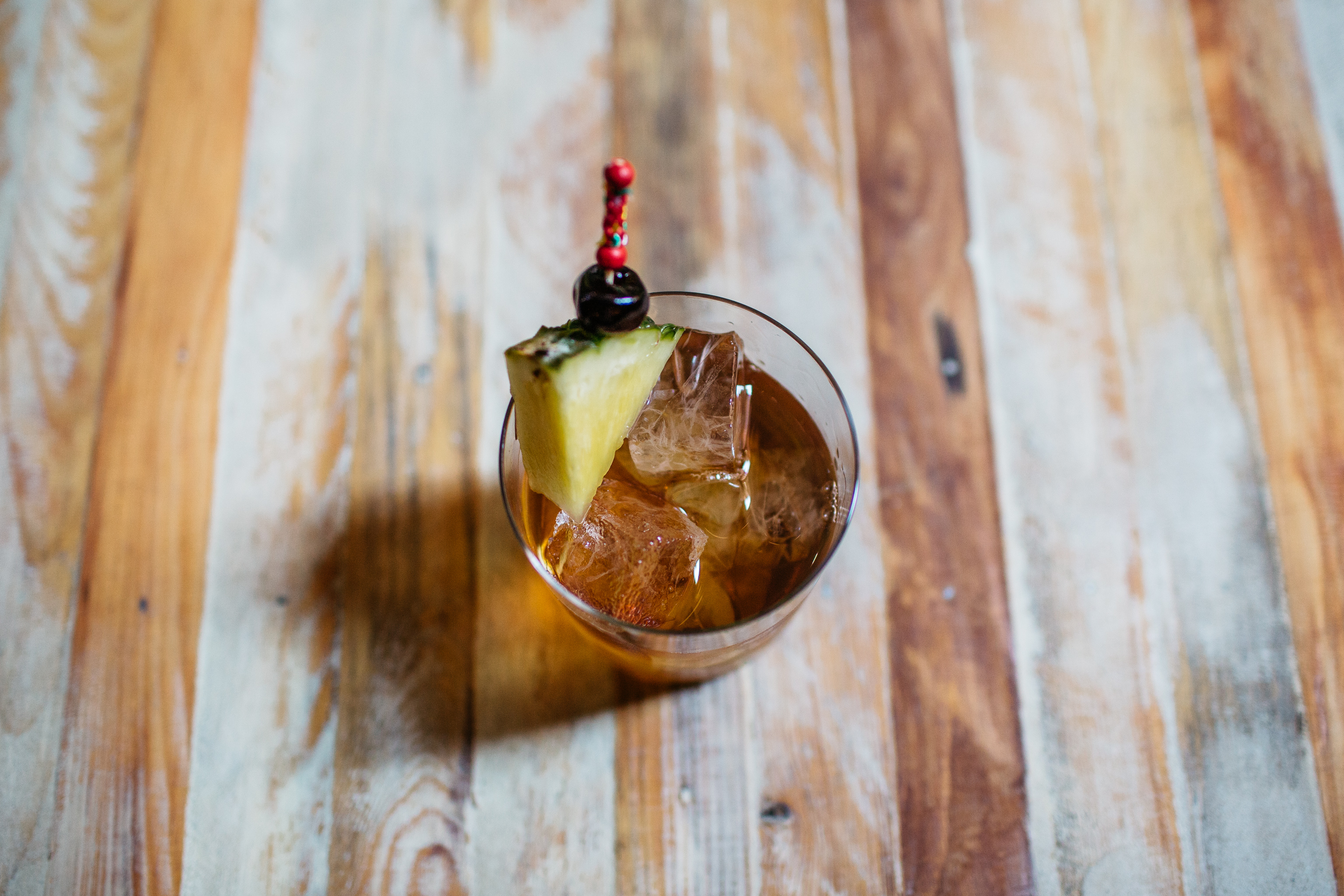 A brown cocktail with ice and a triangle of pineapple.