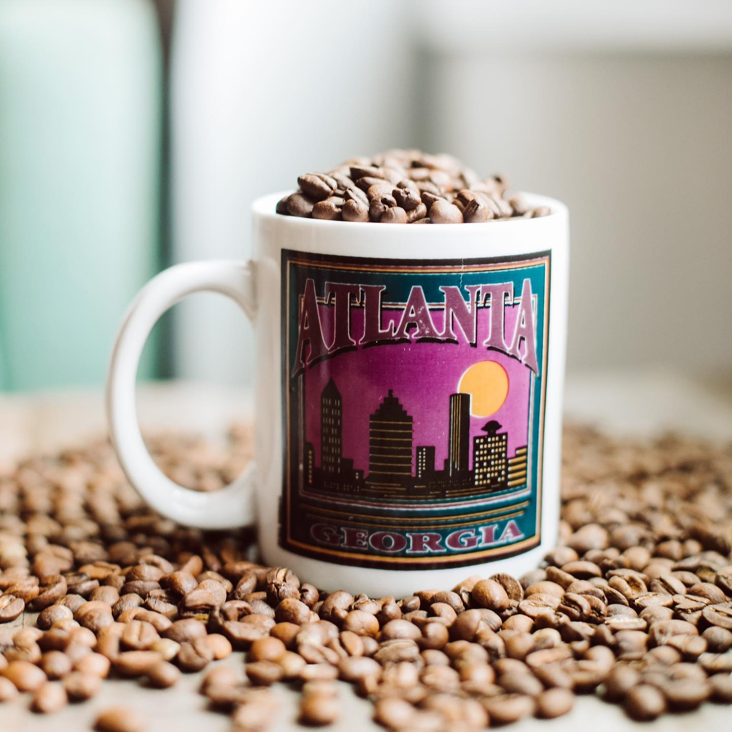 An Atlanta coffee mug filled with coffee beans from Portrait Coffee