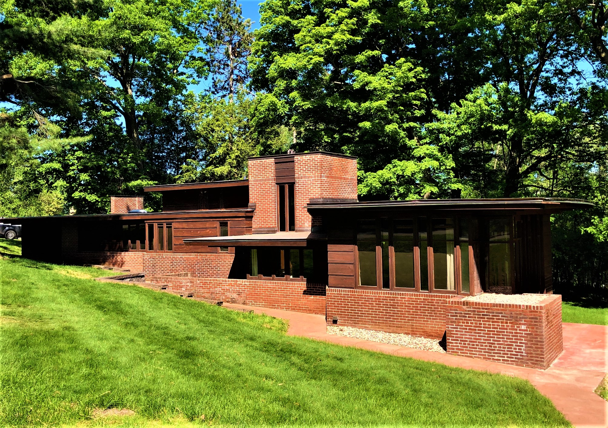 An exterior view of a brick Usonian Frank Lloyd Wright house with green grass in the front and trees in the back.