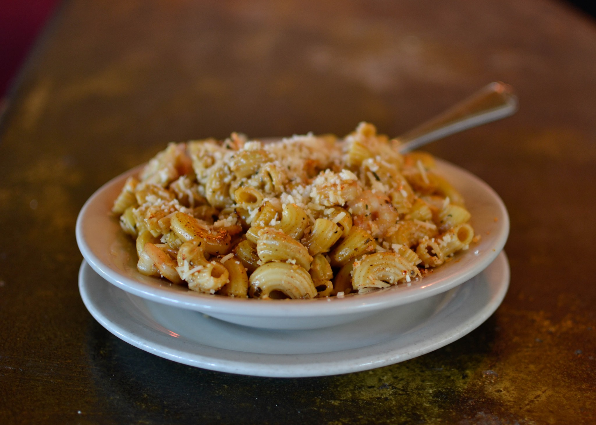 A white bowl of macaroni and cheese sits on a brass counter at Bistro Montage