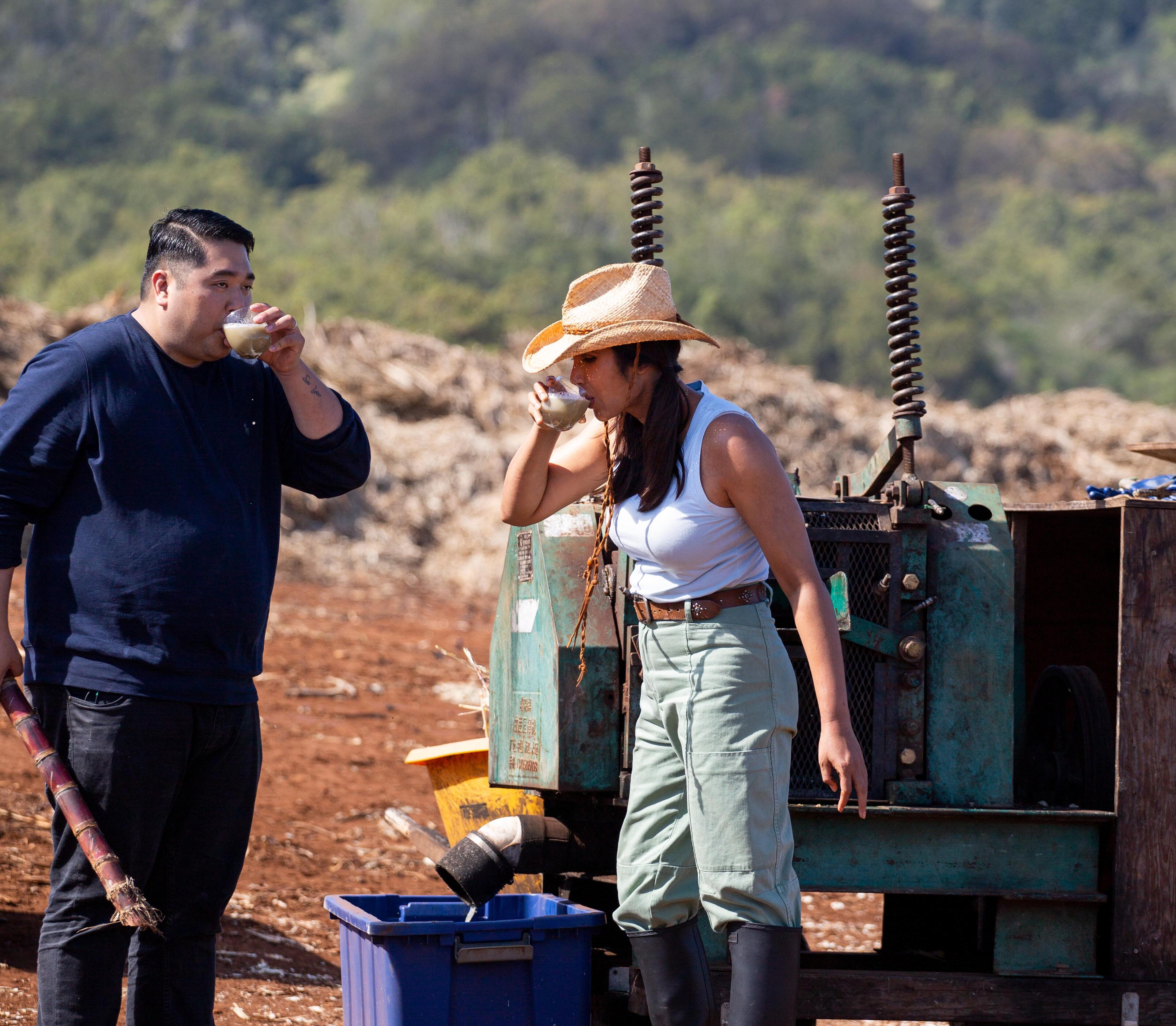 Chris Kajioka (left), in a dark blue shirt and black jeans, and Padma Lakshmi (right), in a white tank top, green cargo pants, boots and a cowboy hat, drink sugar cane juice on a sugar cane farm.