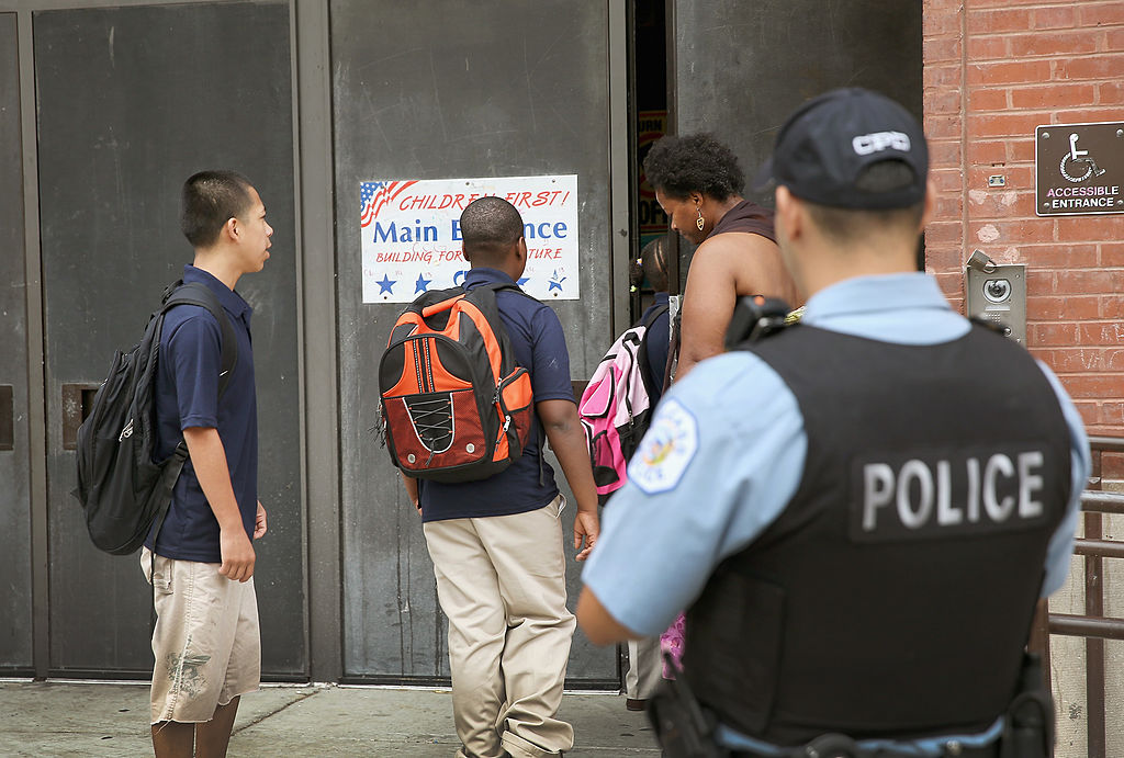 A police officer watched as students arrive to Laura Ward Elementary School on the West Side.
