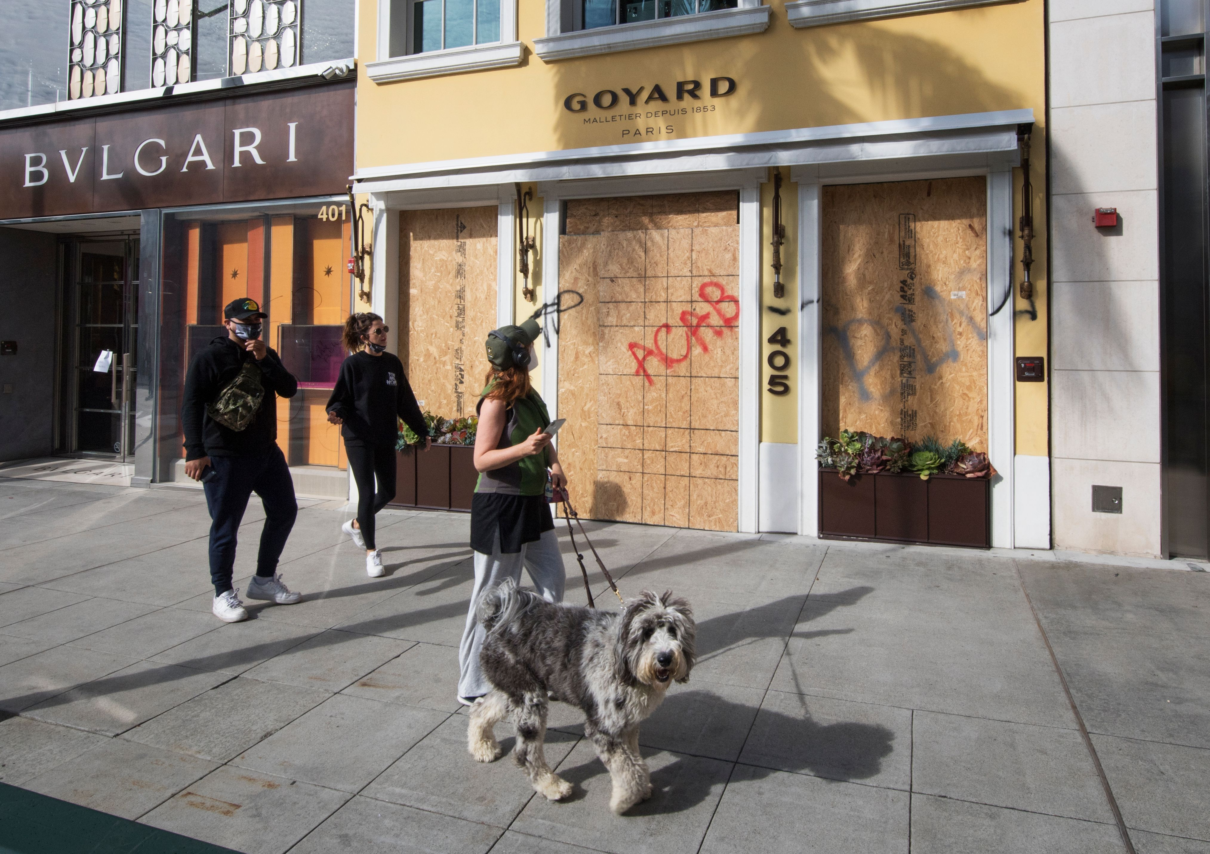 """A woman with a gray white dog on a leash looks up at a boarded up Goyard storefront spray-painted with """"ACAB."""""""