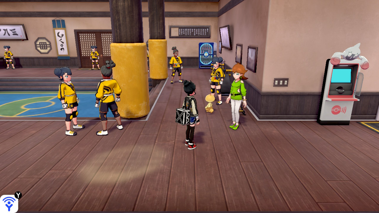 A Pokémon trainer stands in front of Honey in the dojo