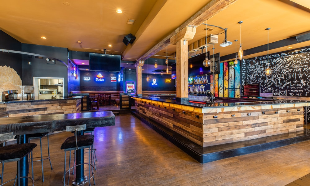 An indoor bar space with tables and neon signs.