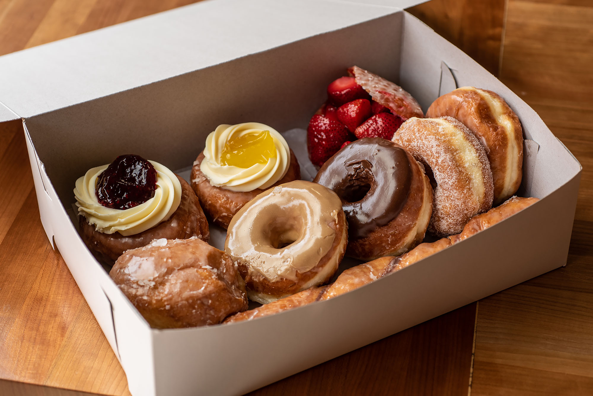 A box of various doughnuts shown from above at an angle, in a white box.