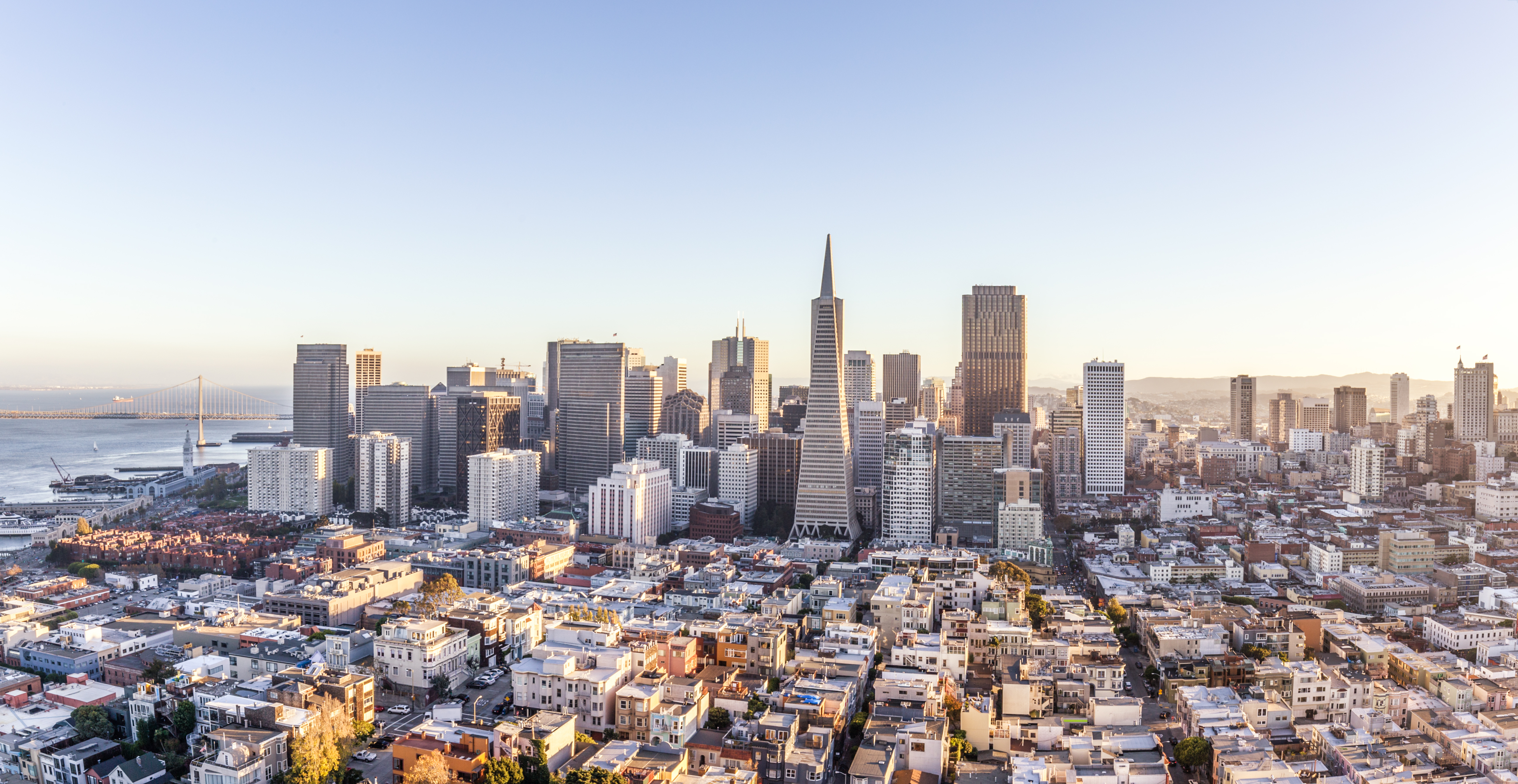 An aerial view of the San Francisco skyline. There are skyscrapers and no clouds in a light blue sky.