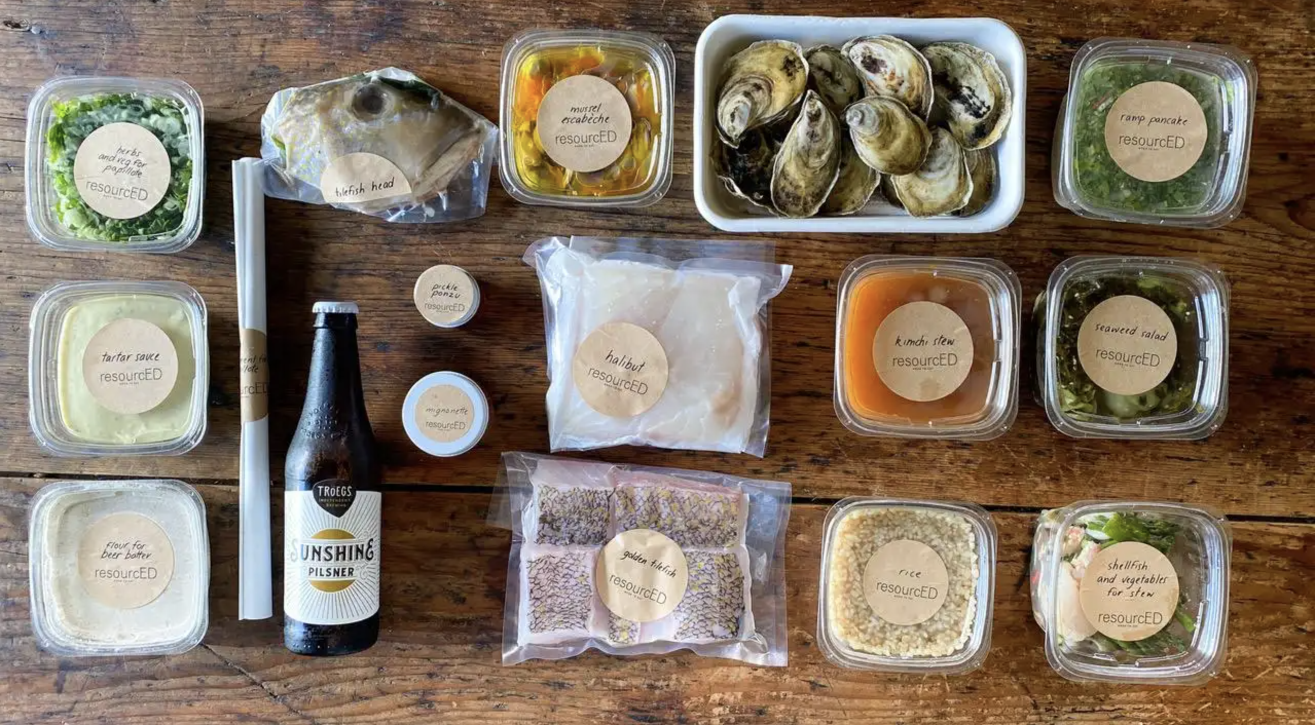 An overhead shot of a table with various food items like oysters and tartar sauce labeled