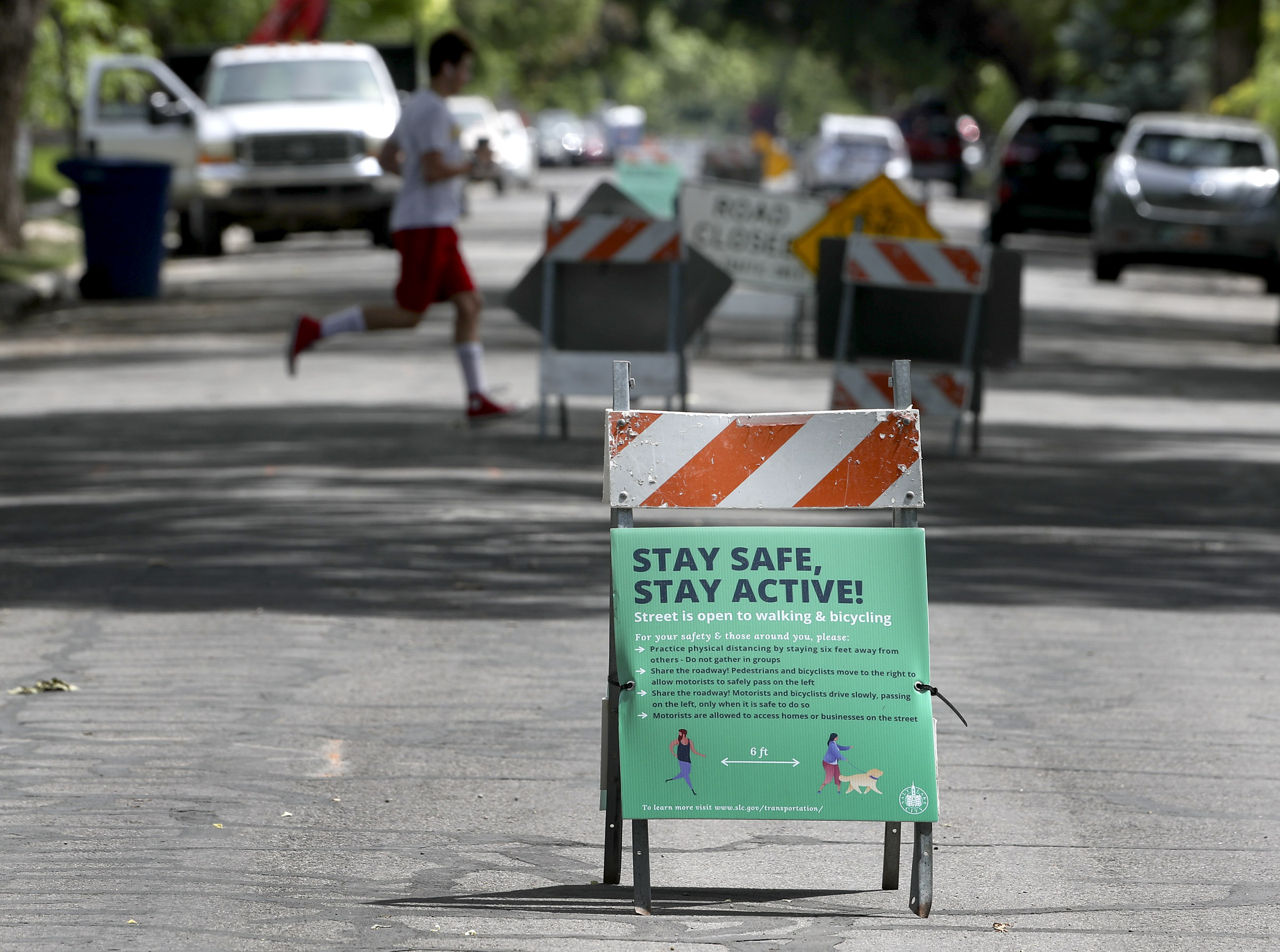 A jogger crosses 800 East near Bryant Avenue in Salt Lake City on Tuesday, June 2, 2020. Several city streets have been closed or restricted to traffic during the coronavirus pandemic. The traffic on 800 East has restricted traffic between 700 South and 1700 South.