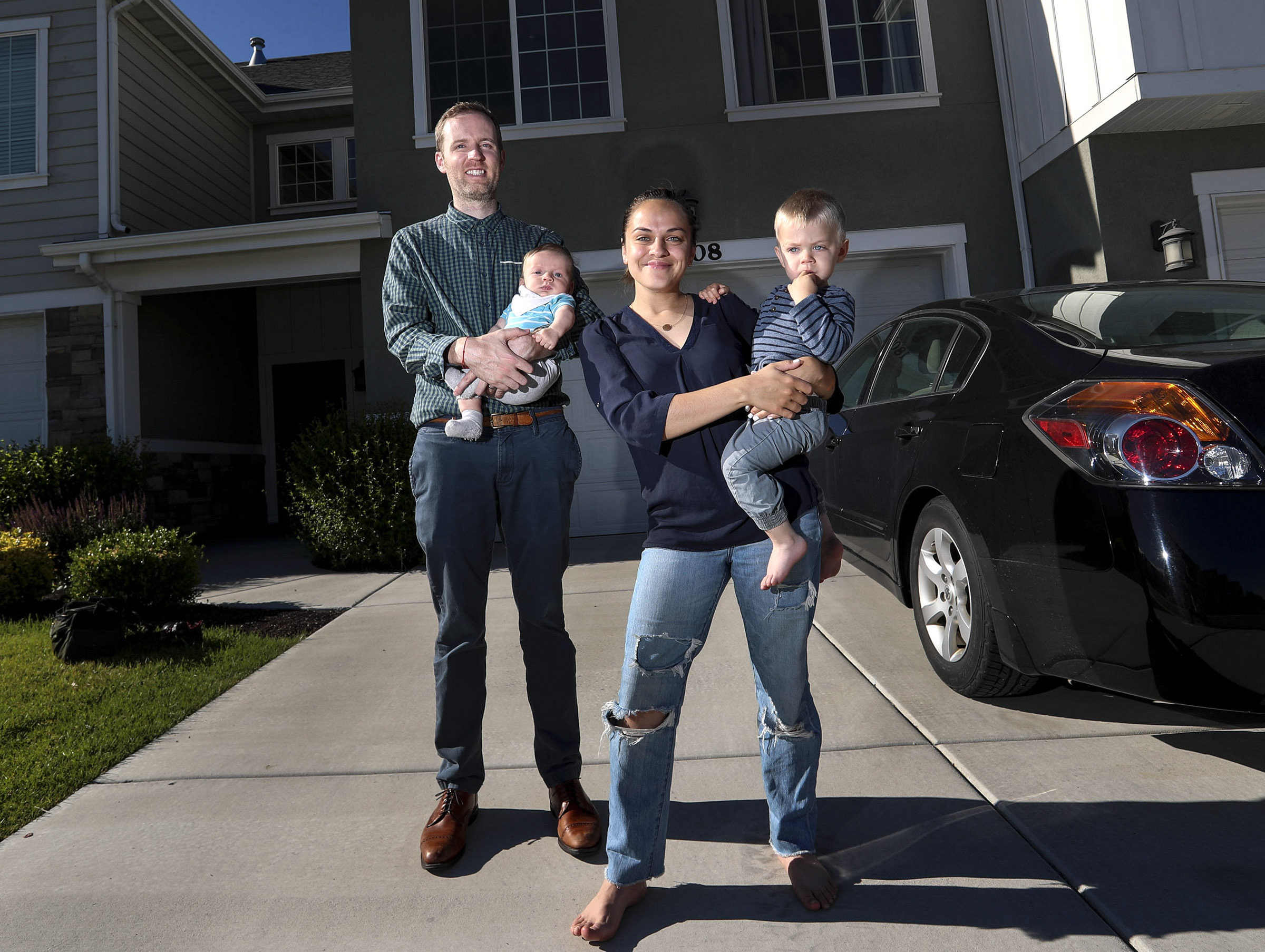 Romina and Lance Harrison hold their sons Ethan and Leo, right, outside their Riverton home on Tuesday, June 9, 2020. The Harrisons purchased a new home in Sandy during the pandemic.
