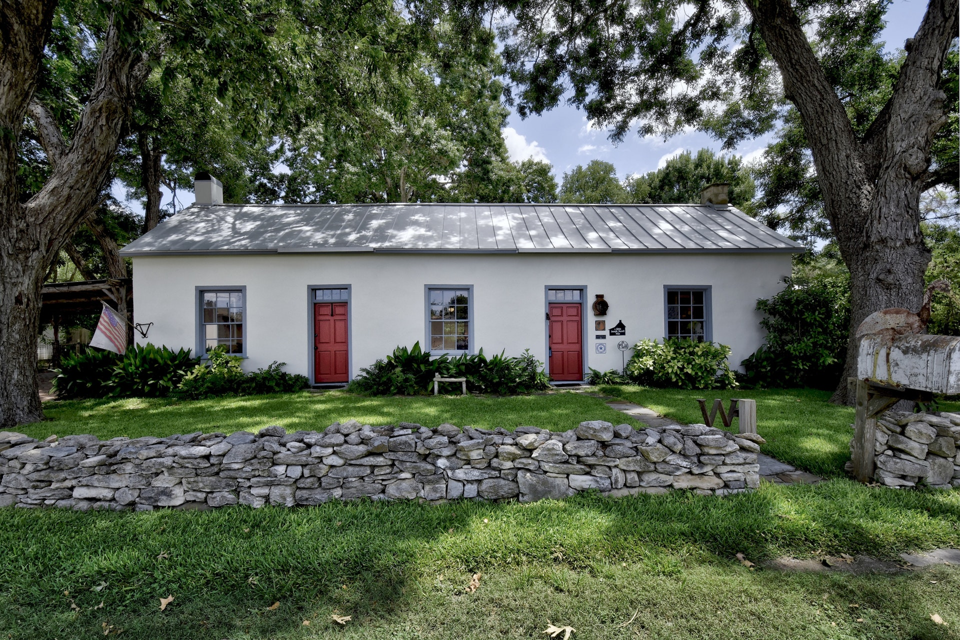 A white, one-story farmhouse for sale has two red doors and is surrounded by green grass and trees. There's a stone wall at the front.