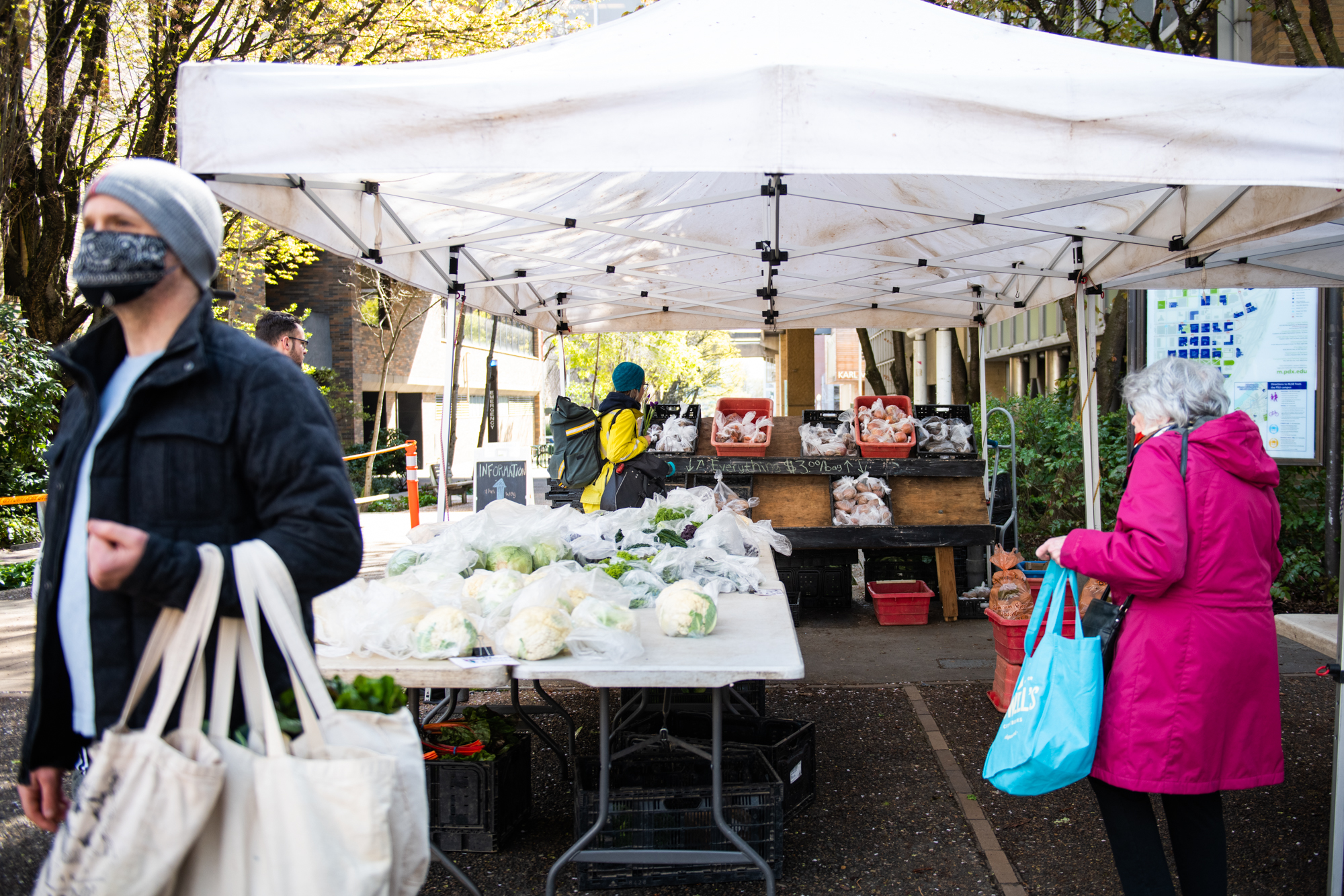 Patrons at the Portland Farmers Market sport masks and practice social distancing as they shop at the Winters Farms stand on Saturday, April 4.