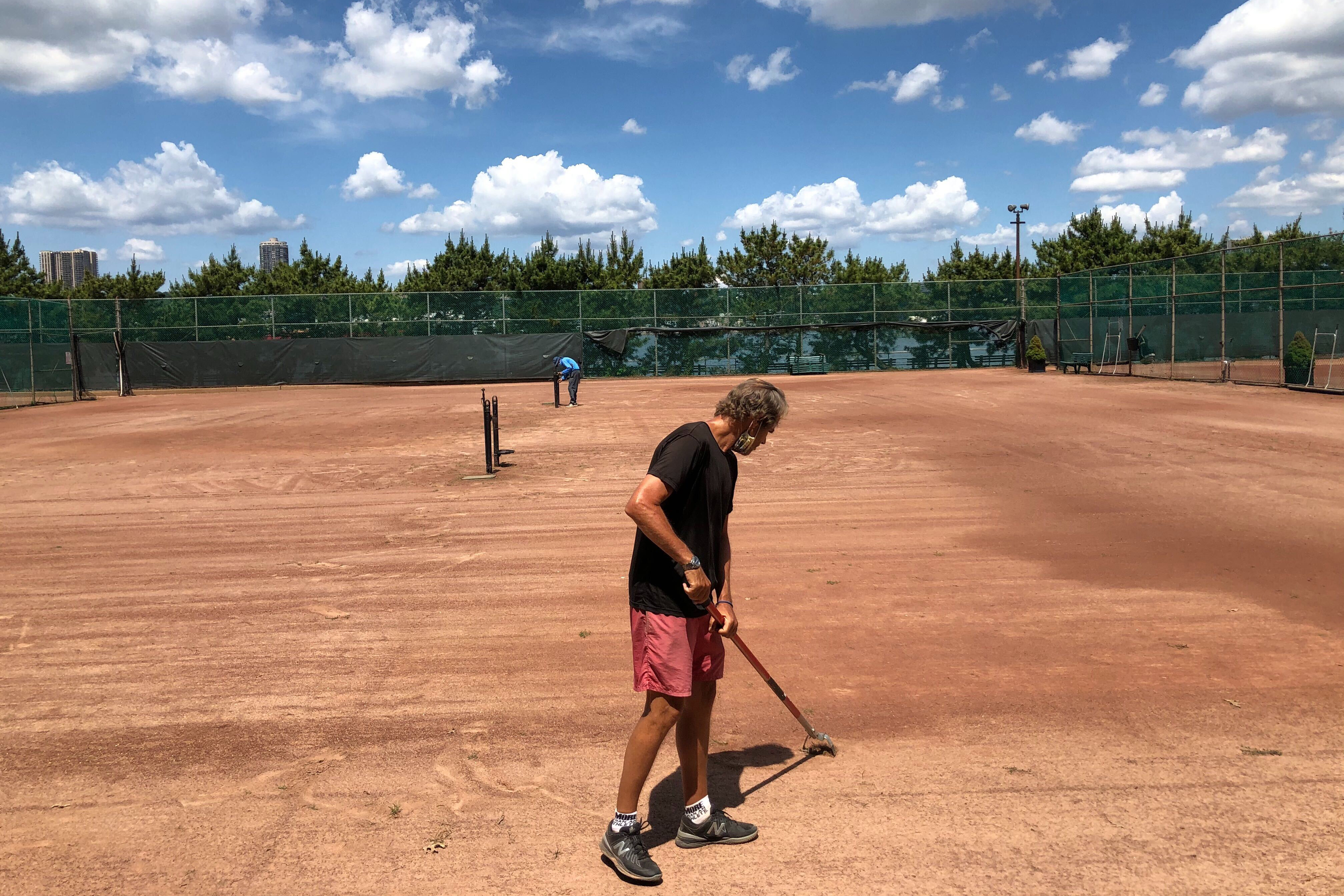 Riverside Clay Tennis Association Associate Director Tim Heath cleans the courts near West 96th Street in preparation for its opening, June 26, 2020.