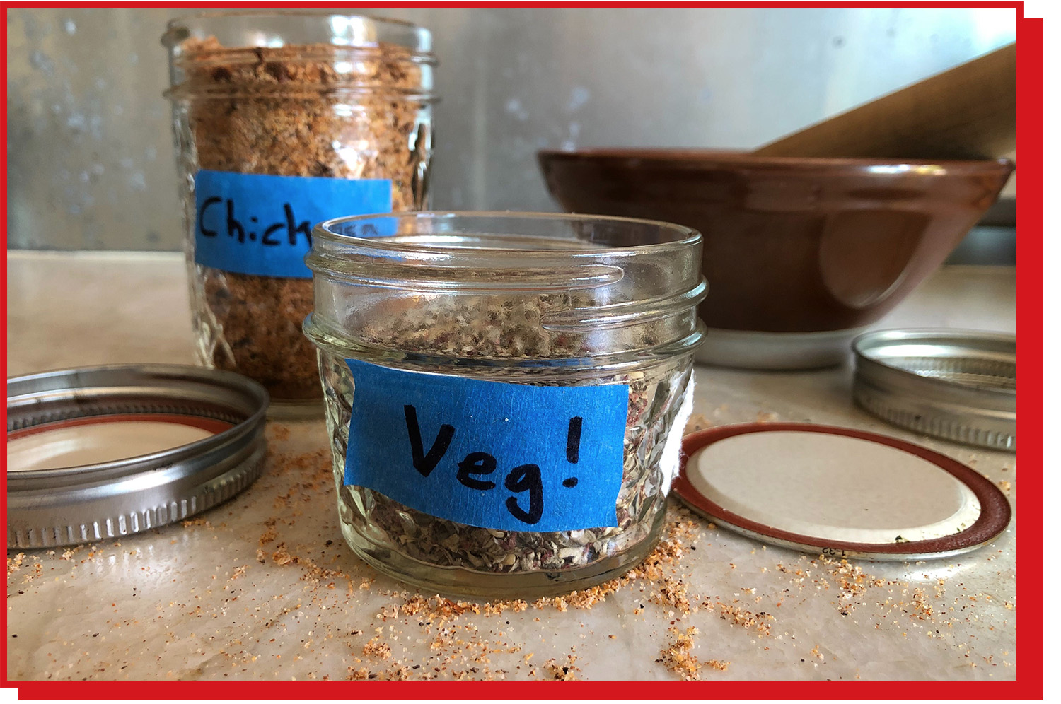 """A small glass container filled with blended spices and a label on the front reading """"Veg!"""""""