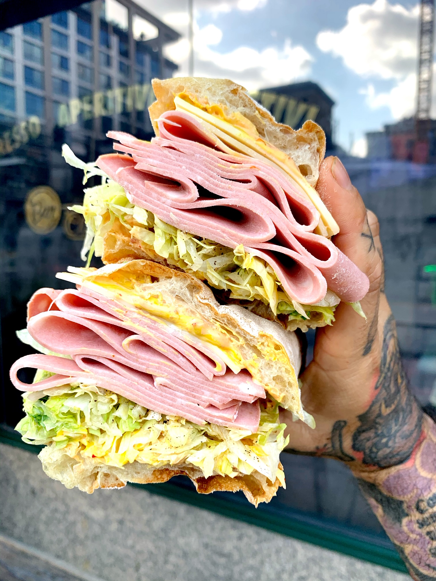 A photo of a man holding a sandwich within which you can see slices of ham, cheese, mustard, and lettuce