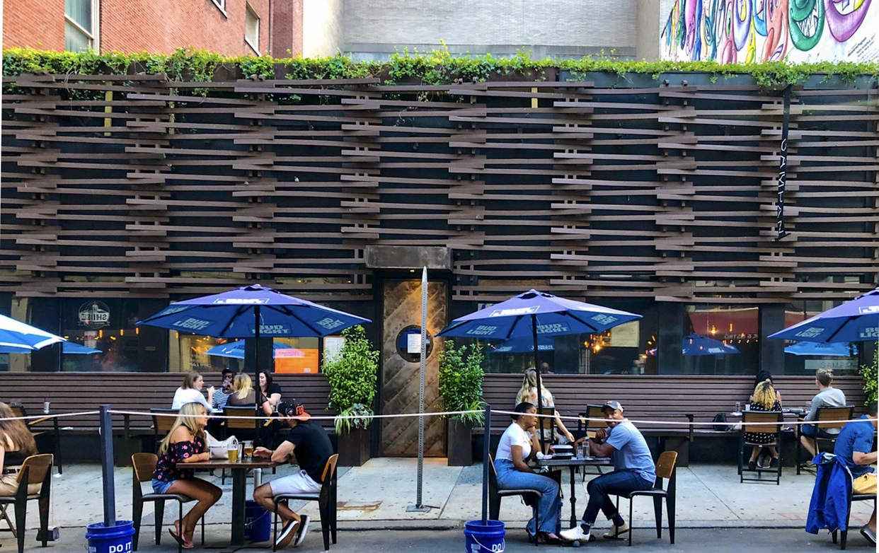 people eating at sidewalk tables with blue umbrellas