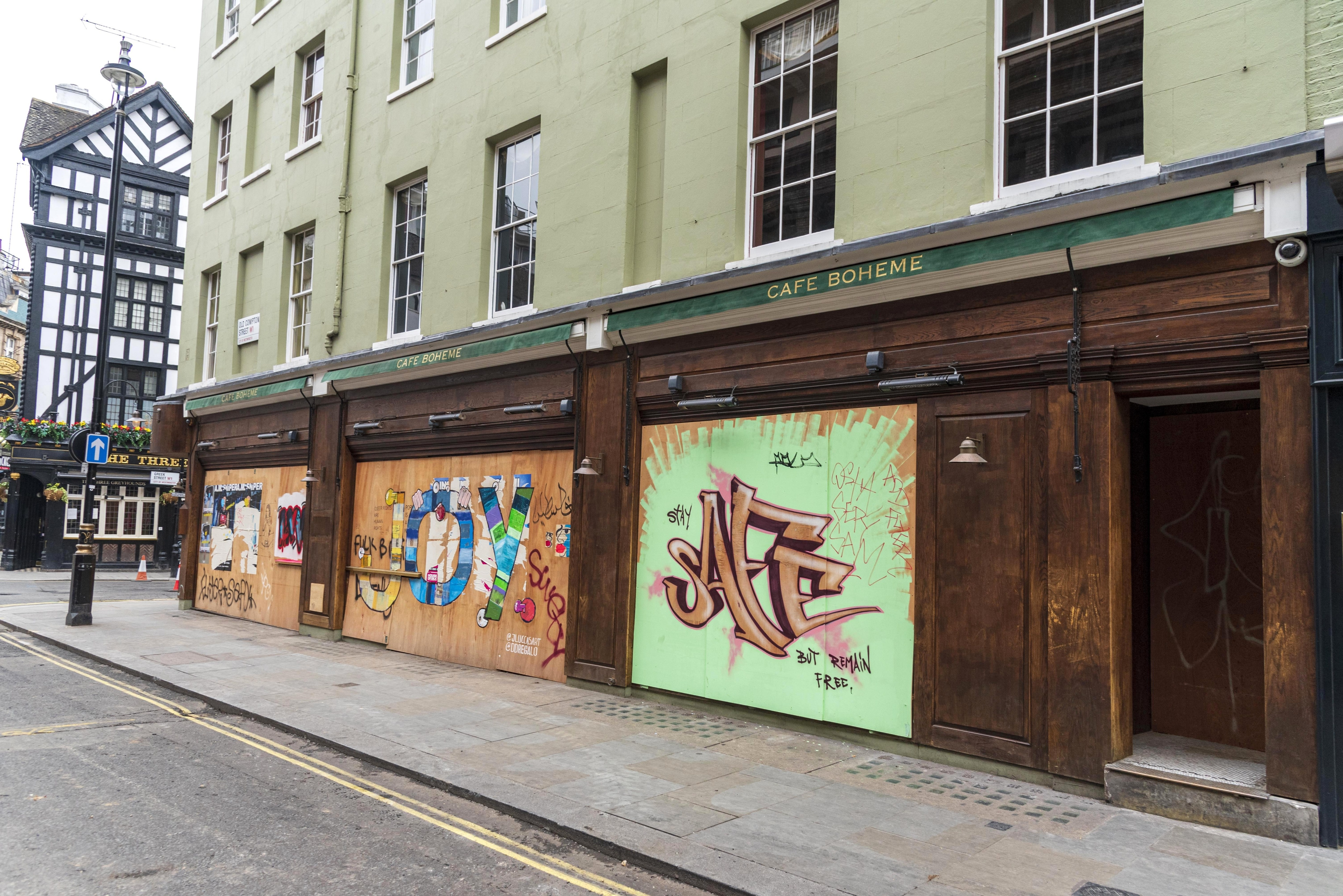Street art on hoardings on the front of Cafe Boheme in Soho...