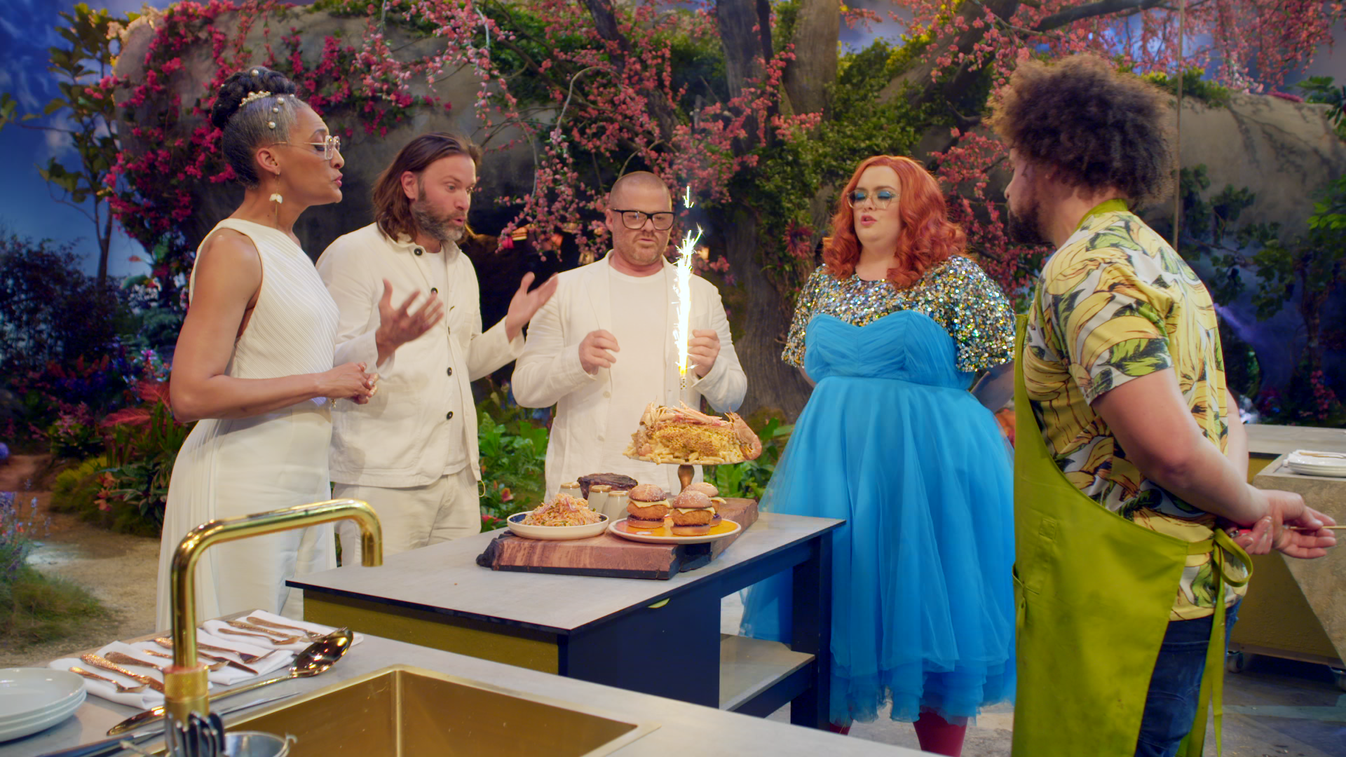 A group stands in a whimsical, Willy Wonka-esque garden, blowing out a sparkler on a cake made of prawns.