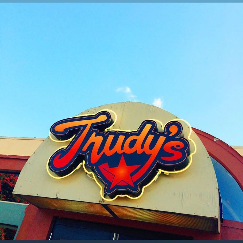 Red sign that says Trudy's with blue sky background