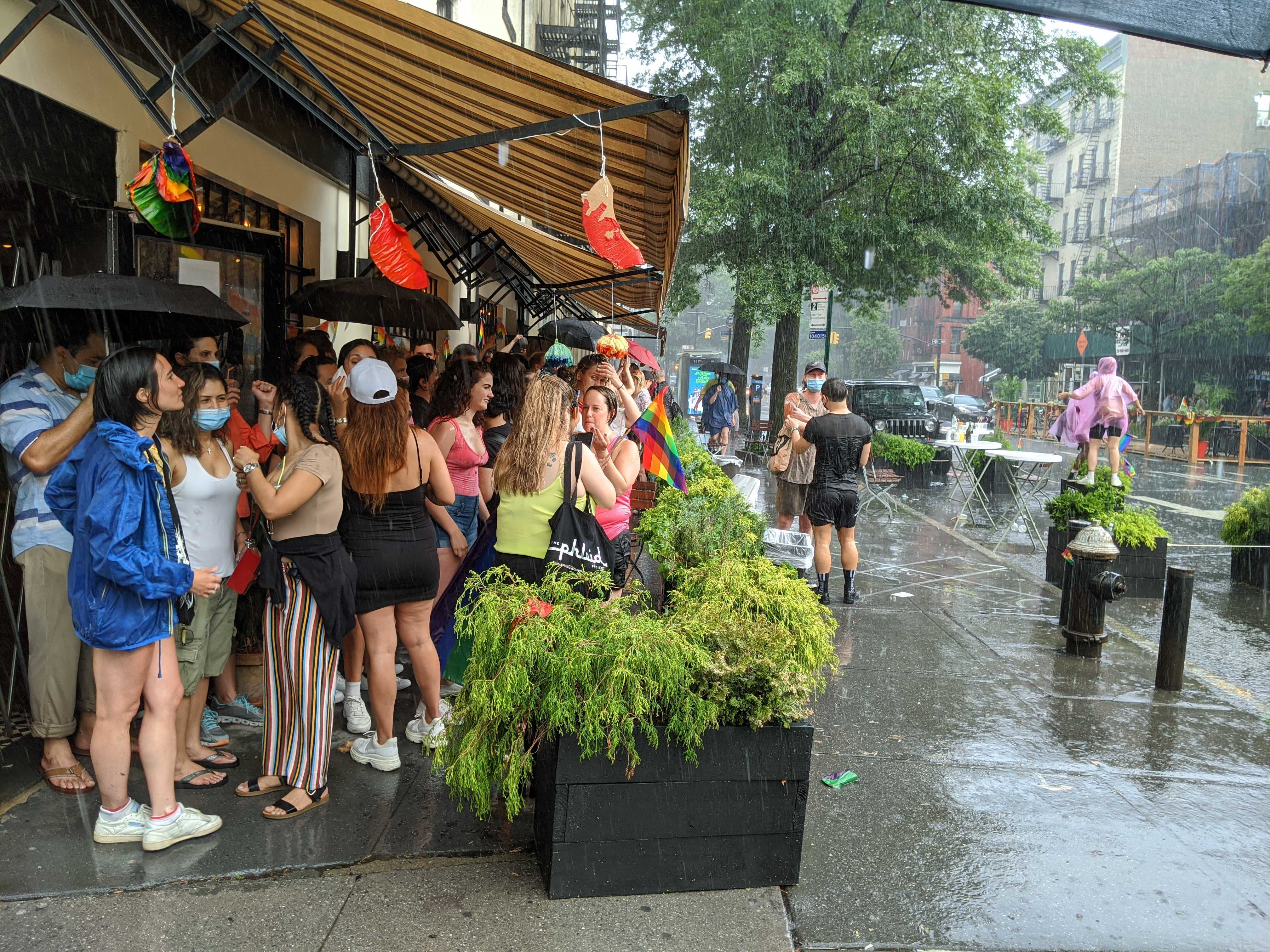 Patrons stand under an awning during a rain shower at Anton's