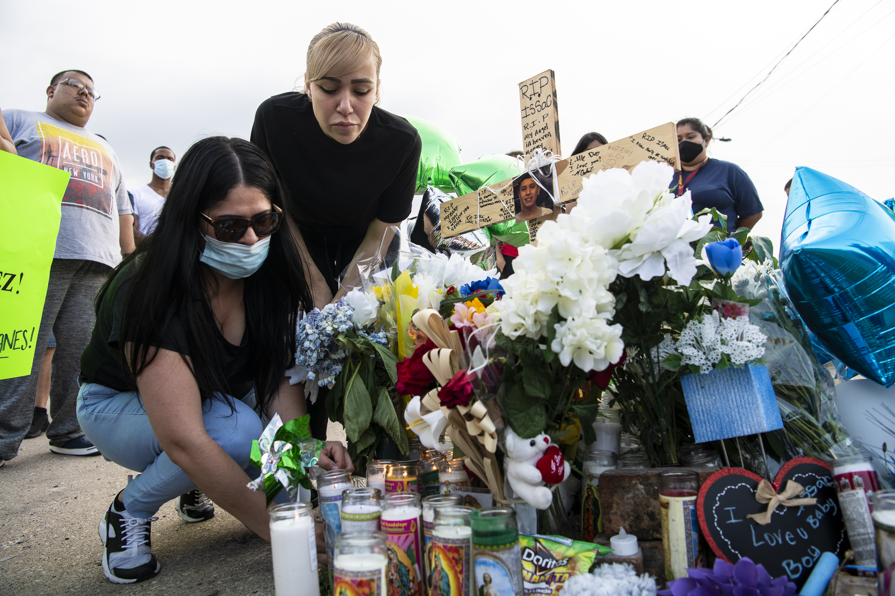 Itzel Dirzo, the mother of Issac Martinez, places flowers at his vigil Tuesday near South Lawndale and West Columbus avenues. Issac, 13, was killed in a hit-and-run while riding his bicycle.