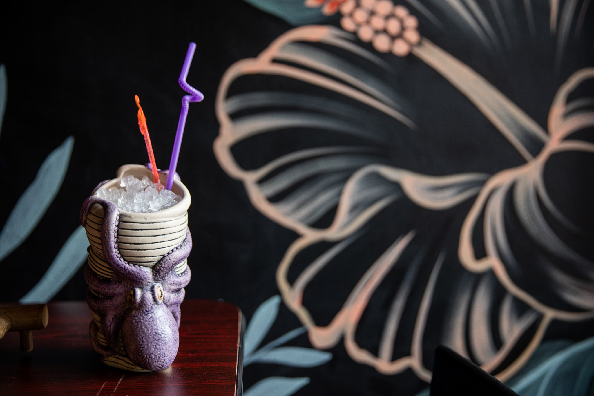 A kraken mug with colorful straws stands in front of a floral mural.