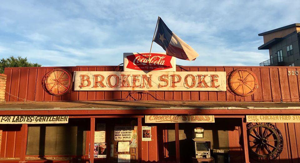 Broken Spoke dance hall storefront with a Texas flag flying overhead on a blue sky