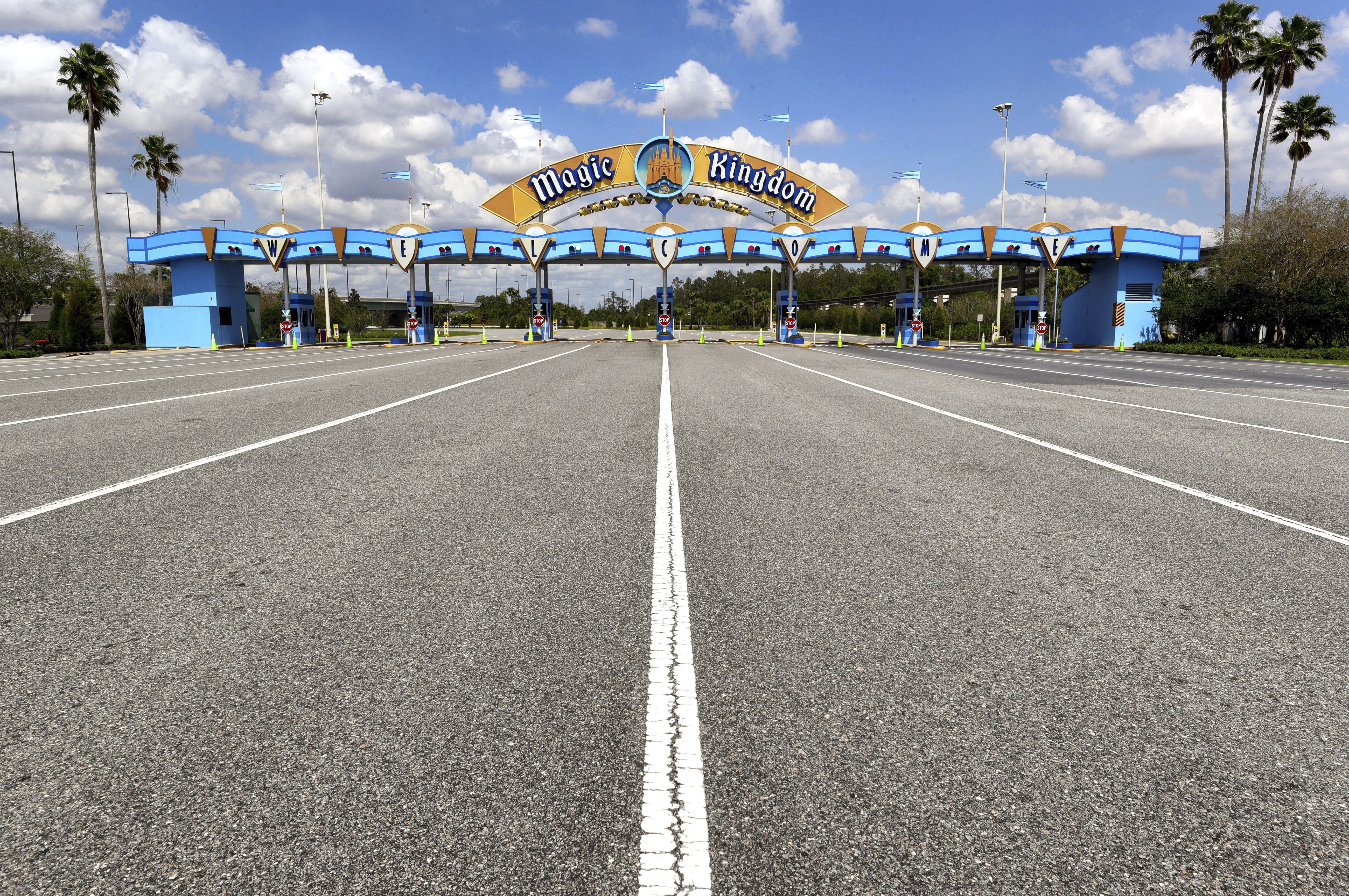In this March 24, 2020, file photo, lanes leading to the parking plaza entrance of Walt Disney World's Magic Kingdom sit empty during its second week of closure in response to the coronavirus pandemic in Orlando.